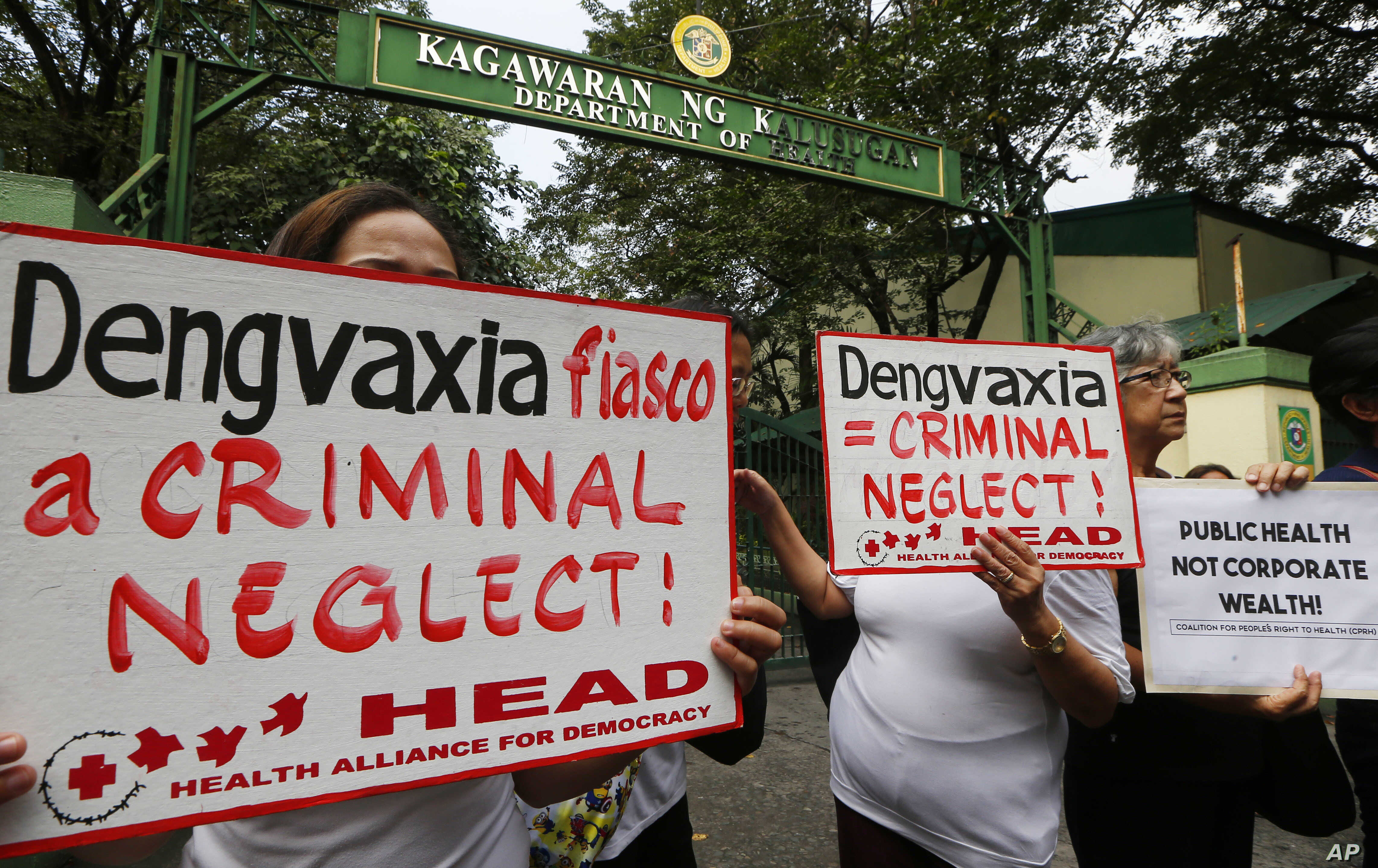 FILE - Protesters display placards during a rally outside the Department of Health as they demand accountability for government officials involved in the controversial immunization of the anti-dengue vaccine Dengvaxia to more than 700,000 Filipino ch...