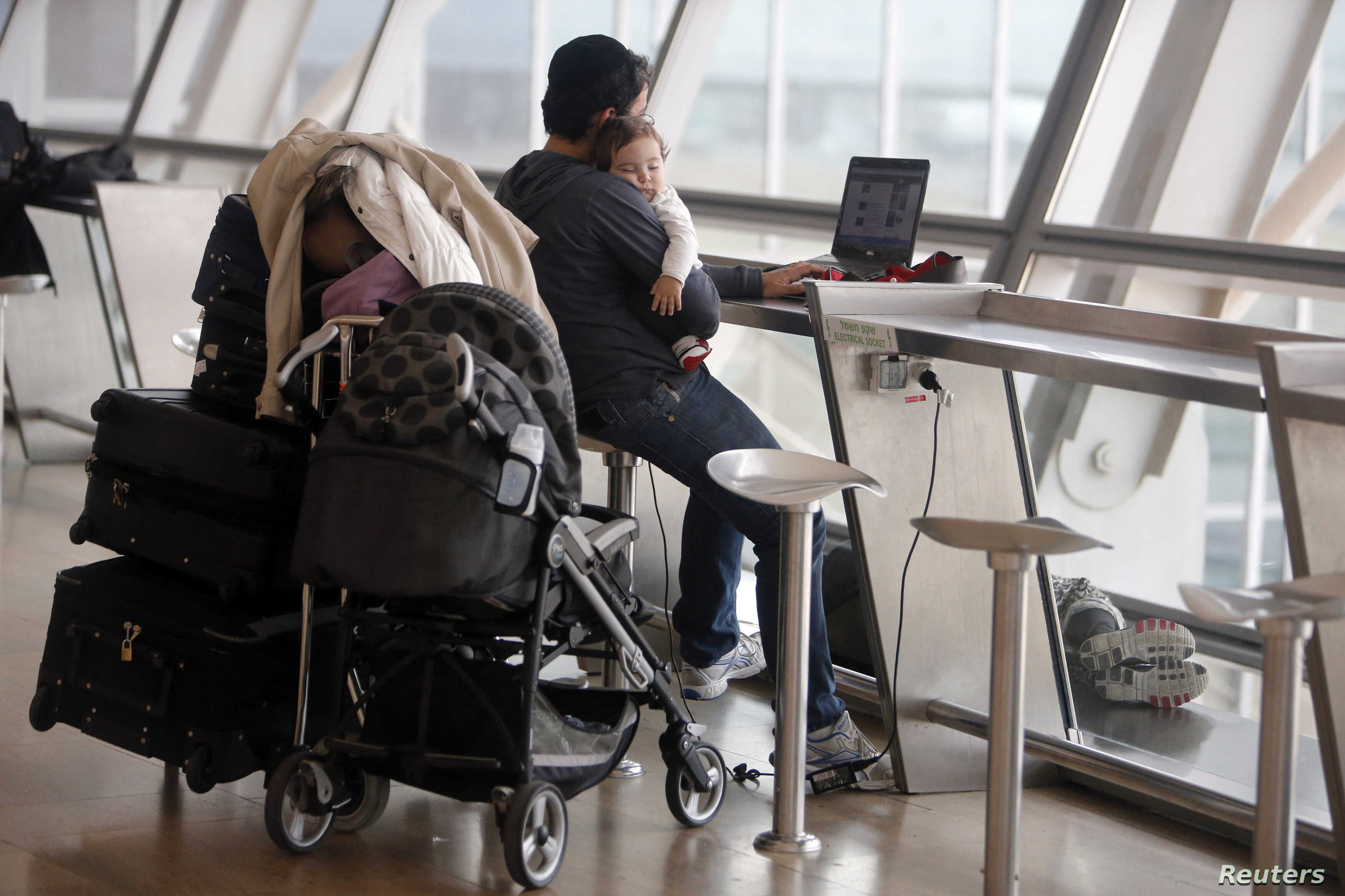 FILE - A passenger holds a baby as he uses his laptop in Israel's Ben-Gurion International Airport near Tel Aviv, April 21, 2013. Men with strollers and on playgrounds are a more common sight now than in their father's generation.