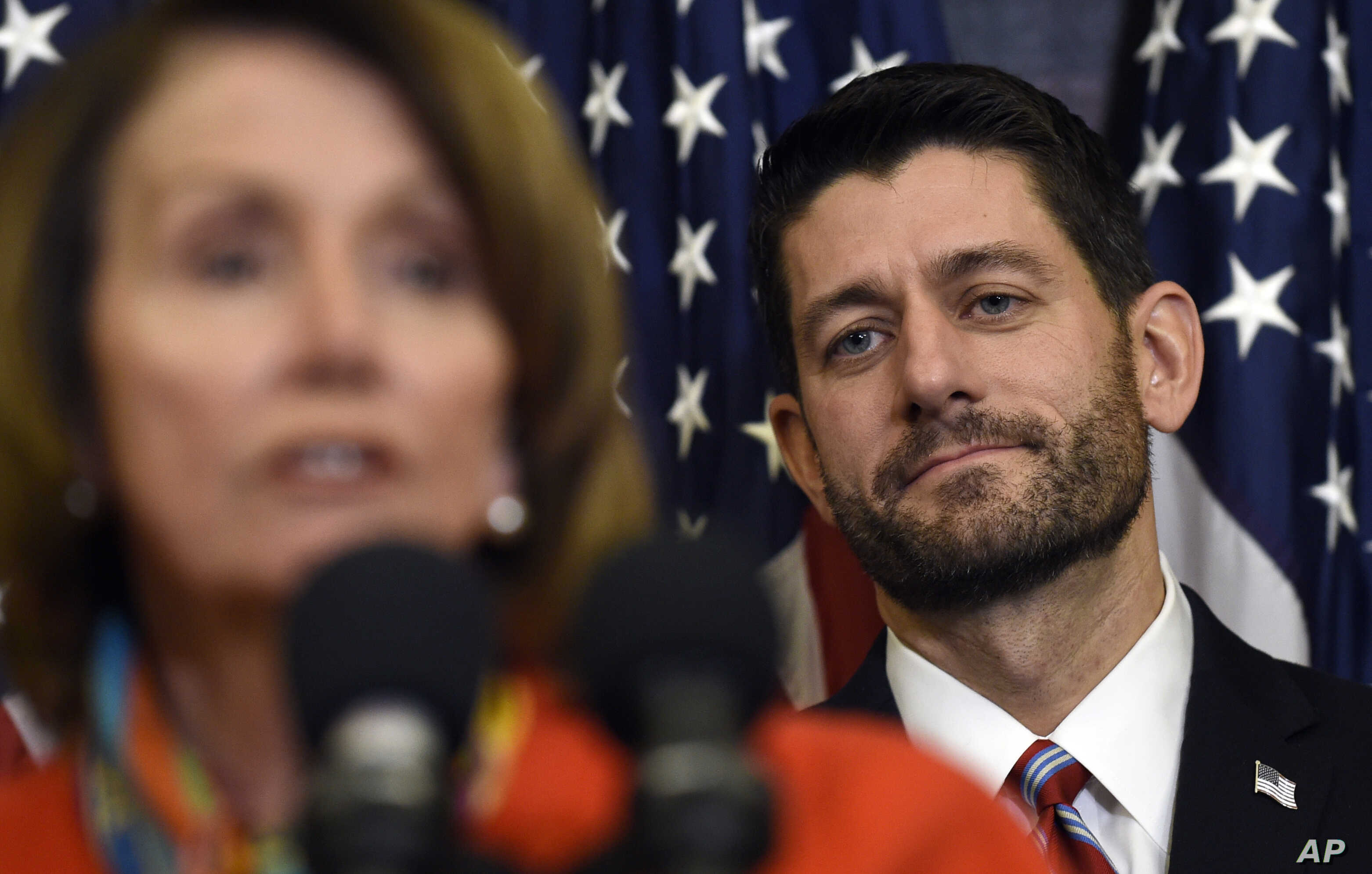 House Speaker Paul Ryan of Wis. listens as House Minority Leader Nancy Pelosi of Calif. speaks on Capitol Hill in Washington, Dec. 9, 2015, before Ryan signed legislation that changes how the nation's public schools are evaluated, rewriting the landm...