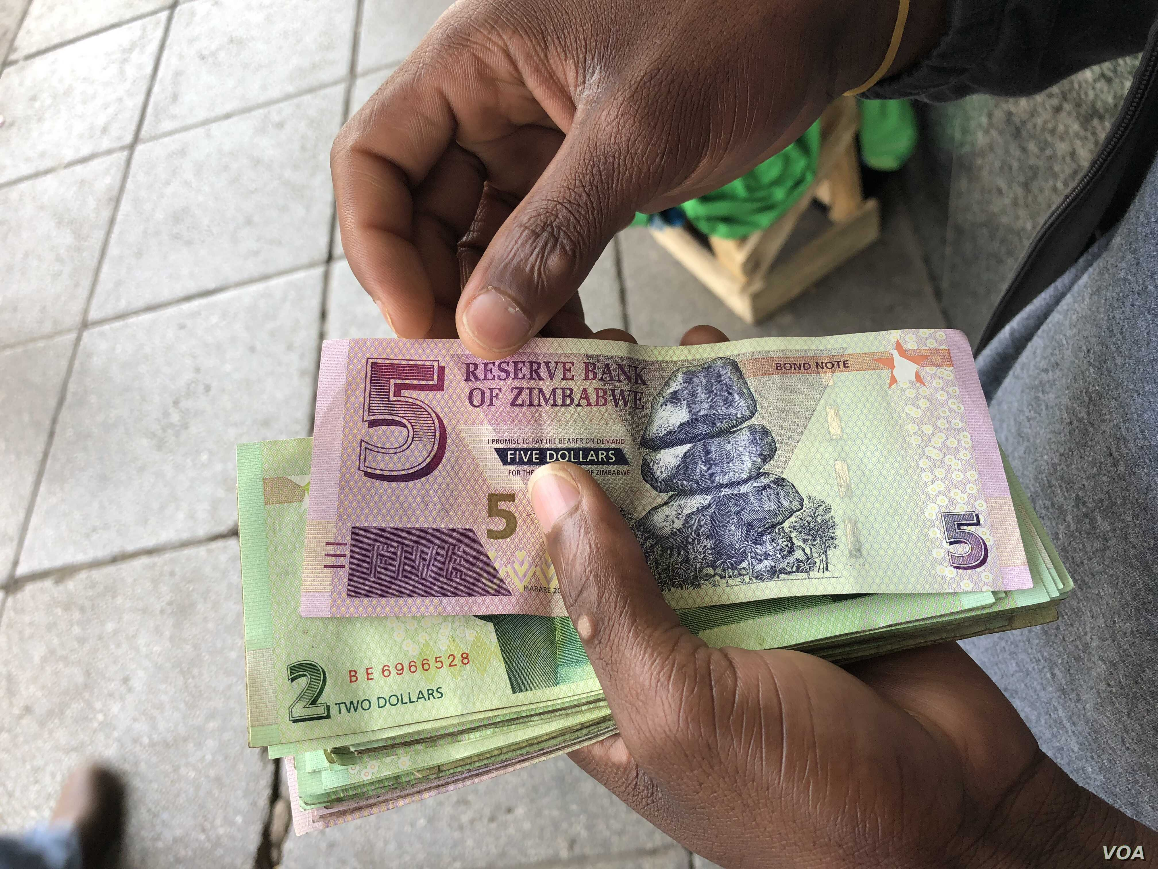 A man in Harare holds bondnotes issued by Reserve Bank of Zimbabwe, Oct. 15, 2018. The introduction of bond notes - a currency Zimbabwe started printing two years ago to ease the situation -- has not helped. (C.Mavhunga/VOA)
