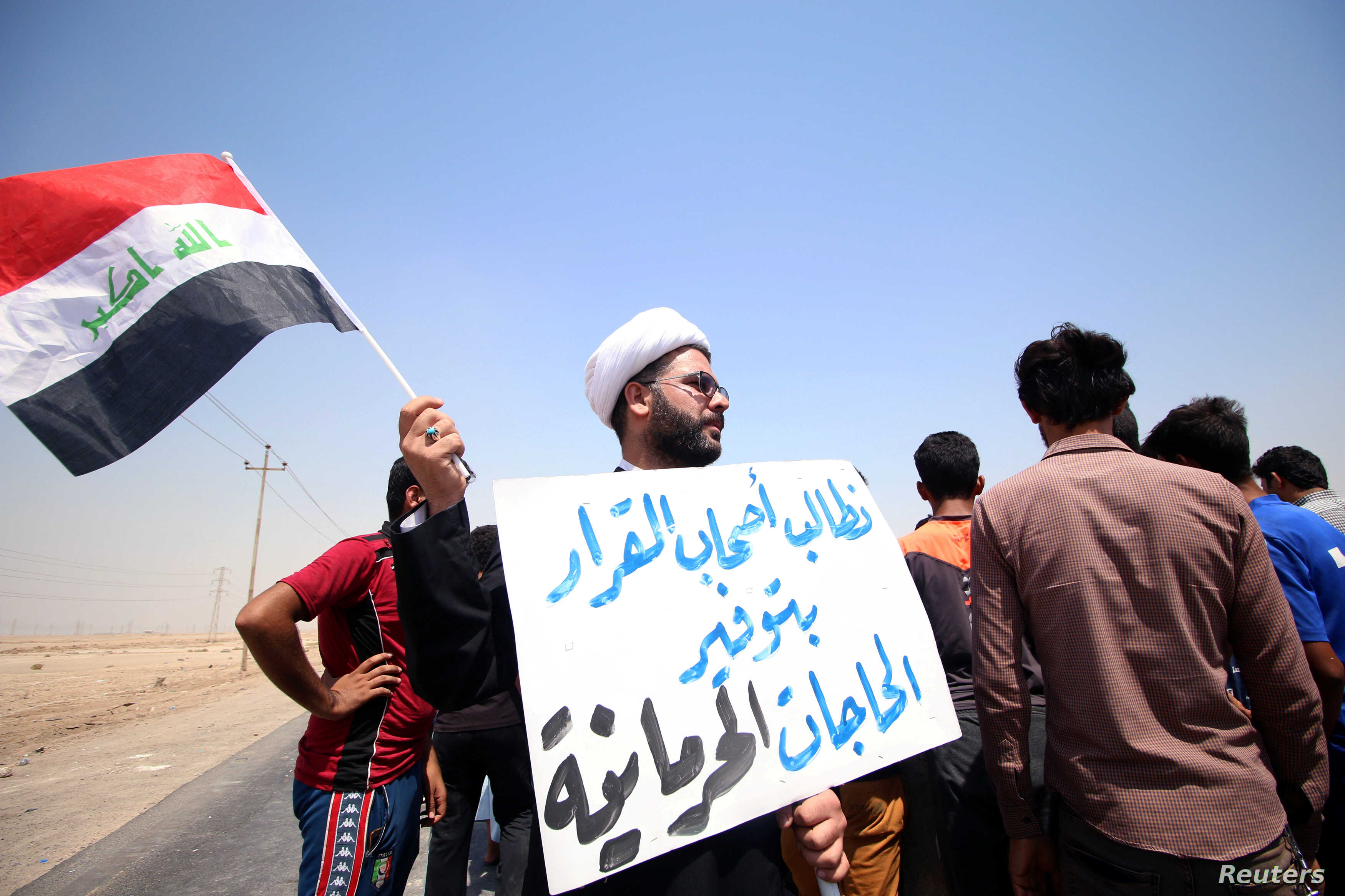 """A protester holds a sign that reads """"We ask the decision makers to provide the things we are deprived of"""" during a protest in south of Basra, Iraq July 16, 2018."""