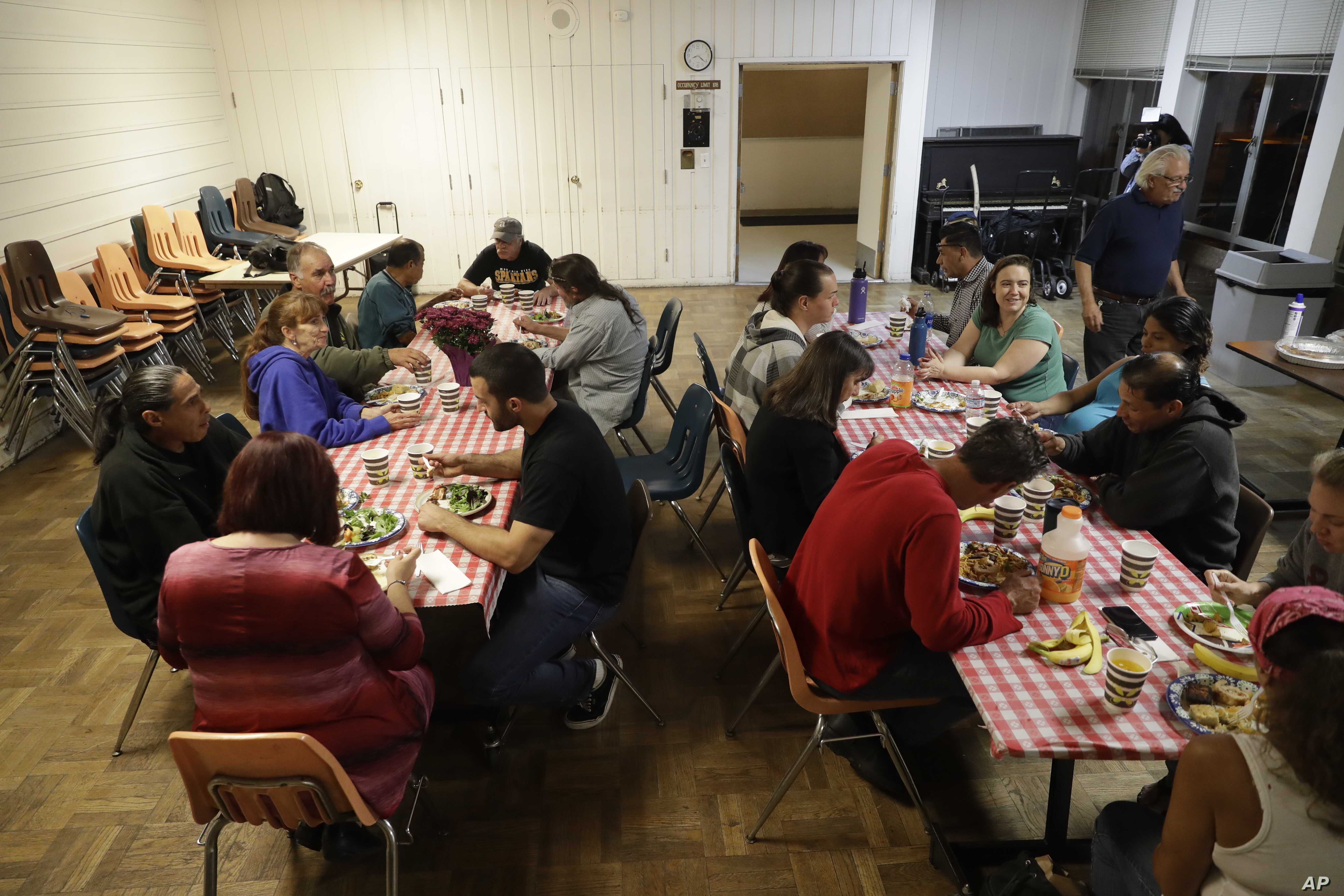 FILE - A group of homeless people, including Ellen Tara James-Penney (wearing blue) left, a lecturer at San Jose State University, receive a meal at Grace Baptist Church in San Jose, California, Oct. 10, 2017.