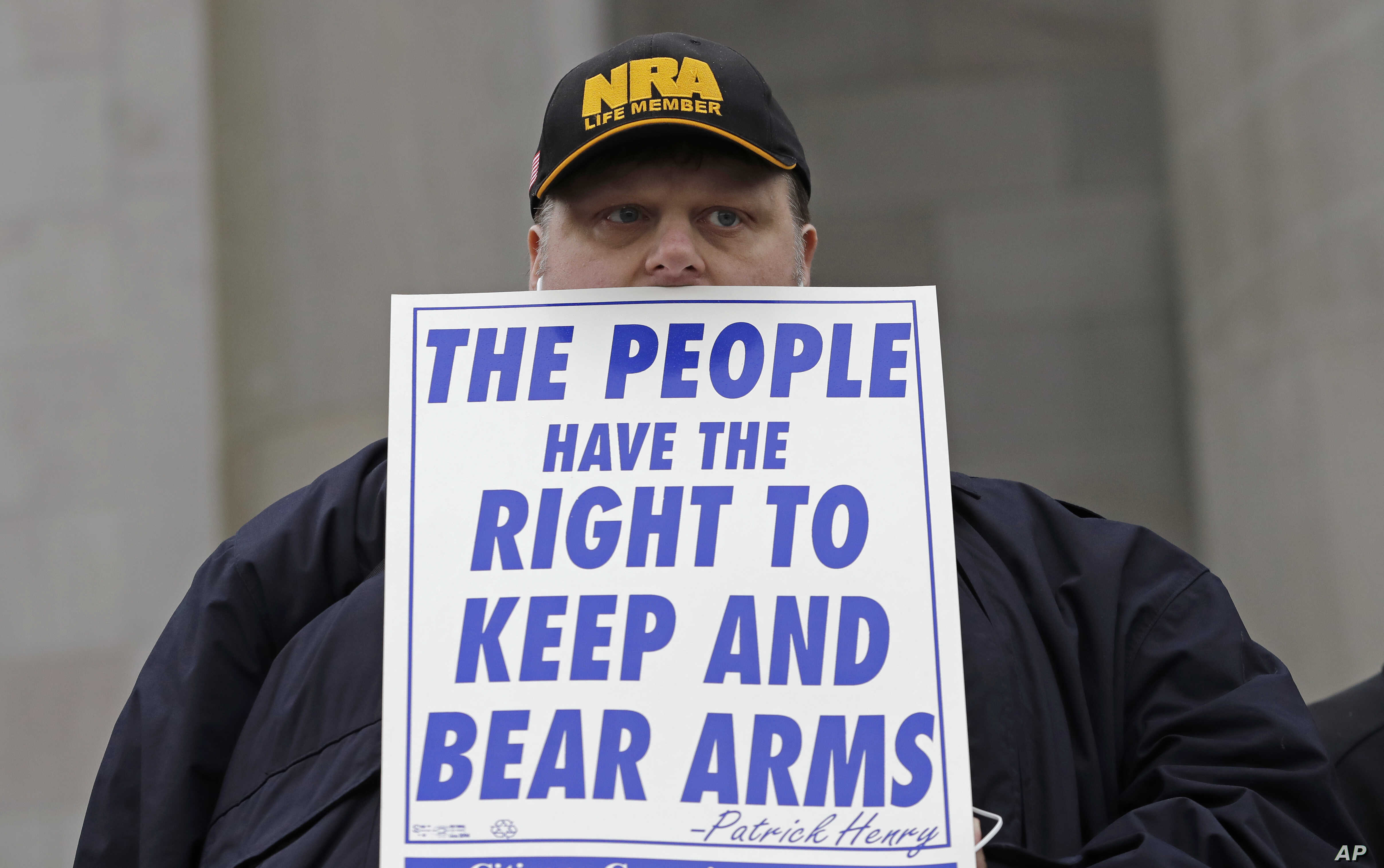 """FILE - John Doll, of Renton, Wash., holds a sign that reads """"The people have the right to keep and bear arms"""" during a gun rights rally at the Capitol in Olympia, Wash."""