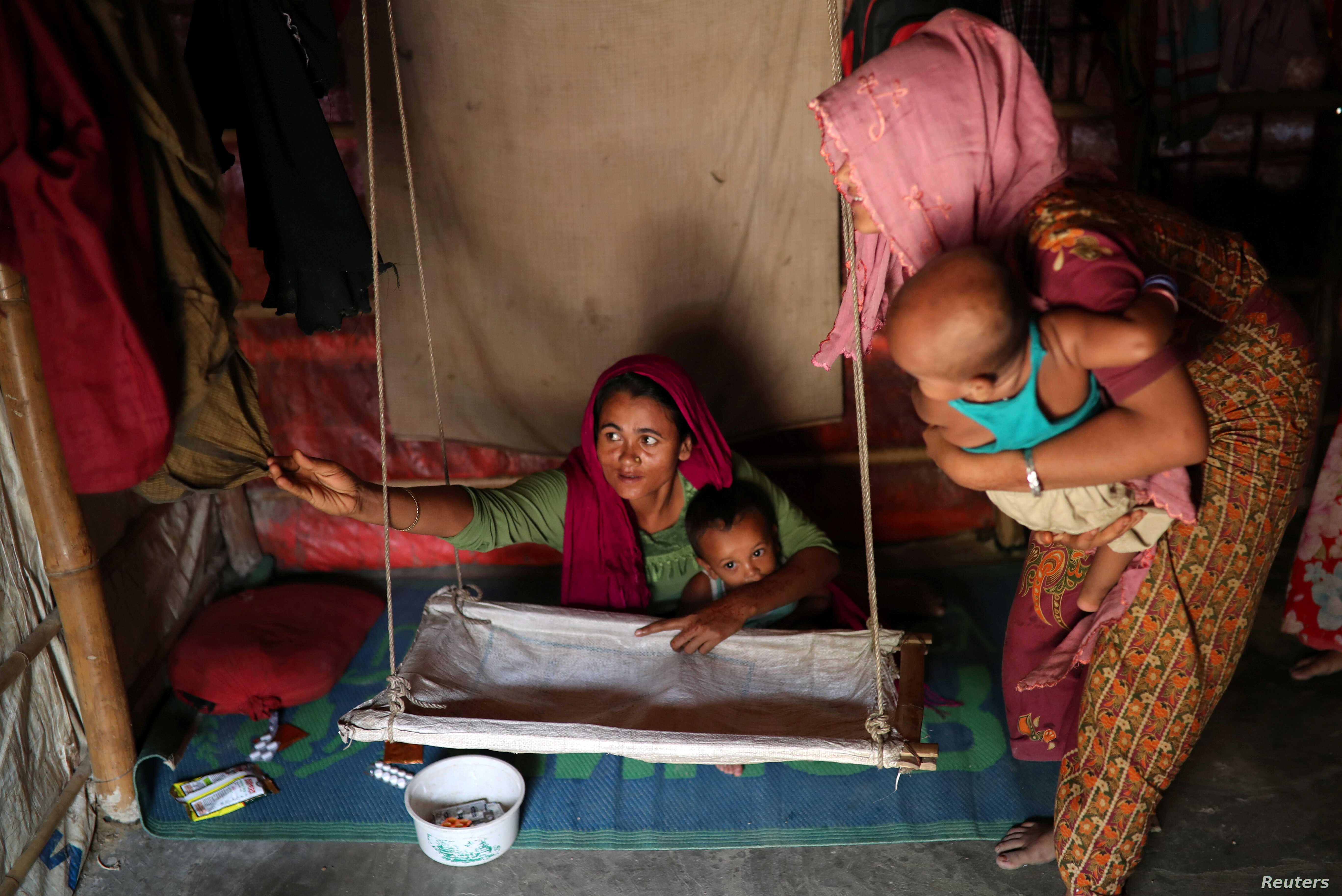 Rohingya refugee women arrange a cradle for child in their makeshift tent in the Balukhali refugee camp in Cox's Bazar, Bangladesh, Aug. 23, 2018.
