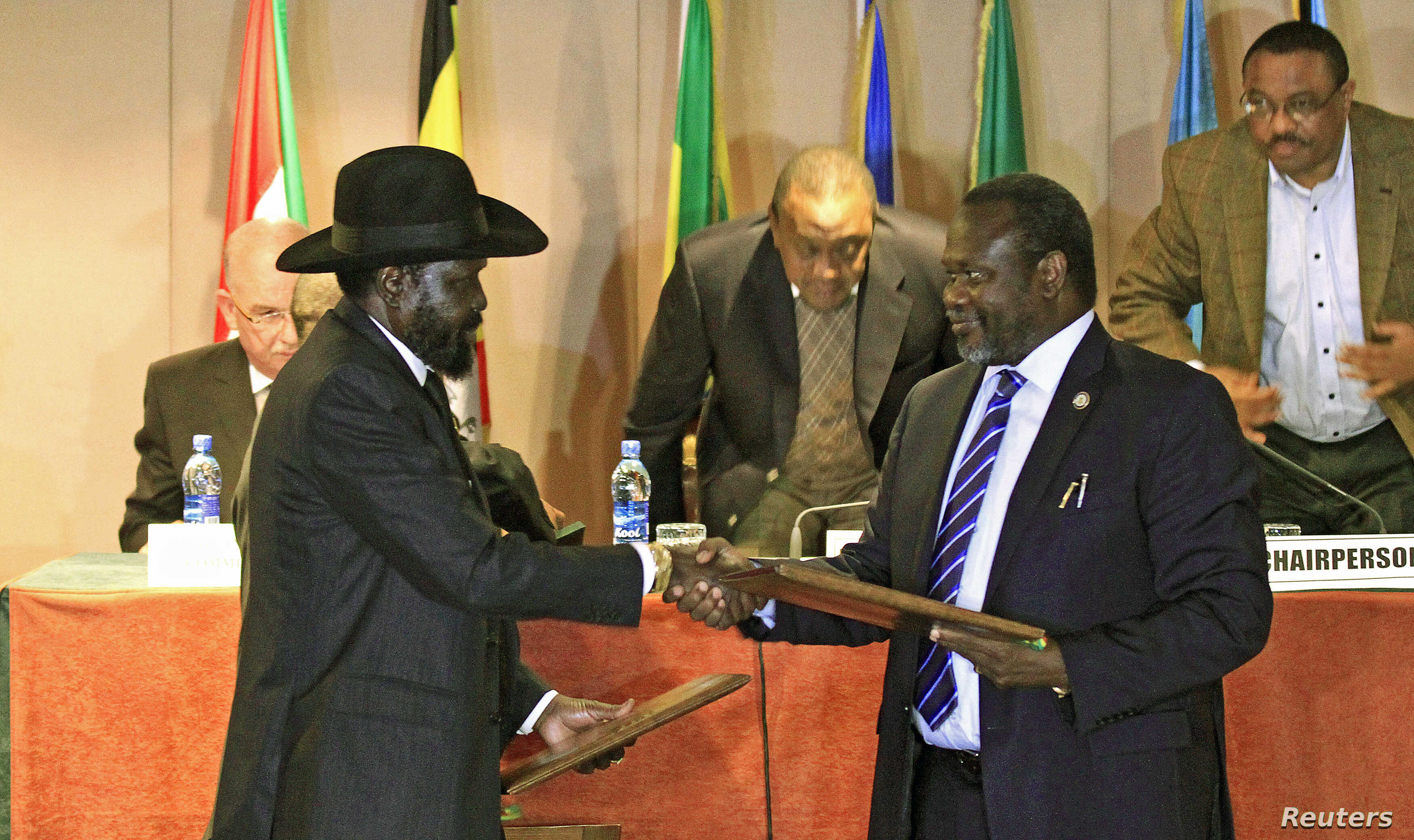 South Sudan's President Salva Kiir (front L) and South Sudan's rebel commander Riek Machar exchange documents after signing a cease-fire agreement during the Inter Governmental Authority on Development (IGAD) Summit on the case of South Sudan in Ethi...