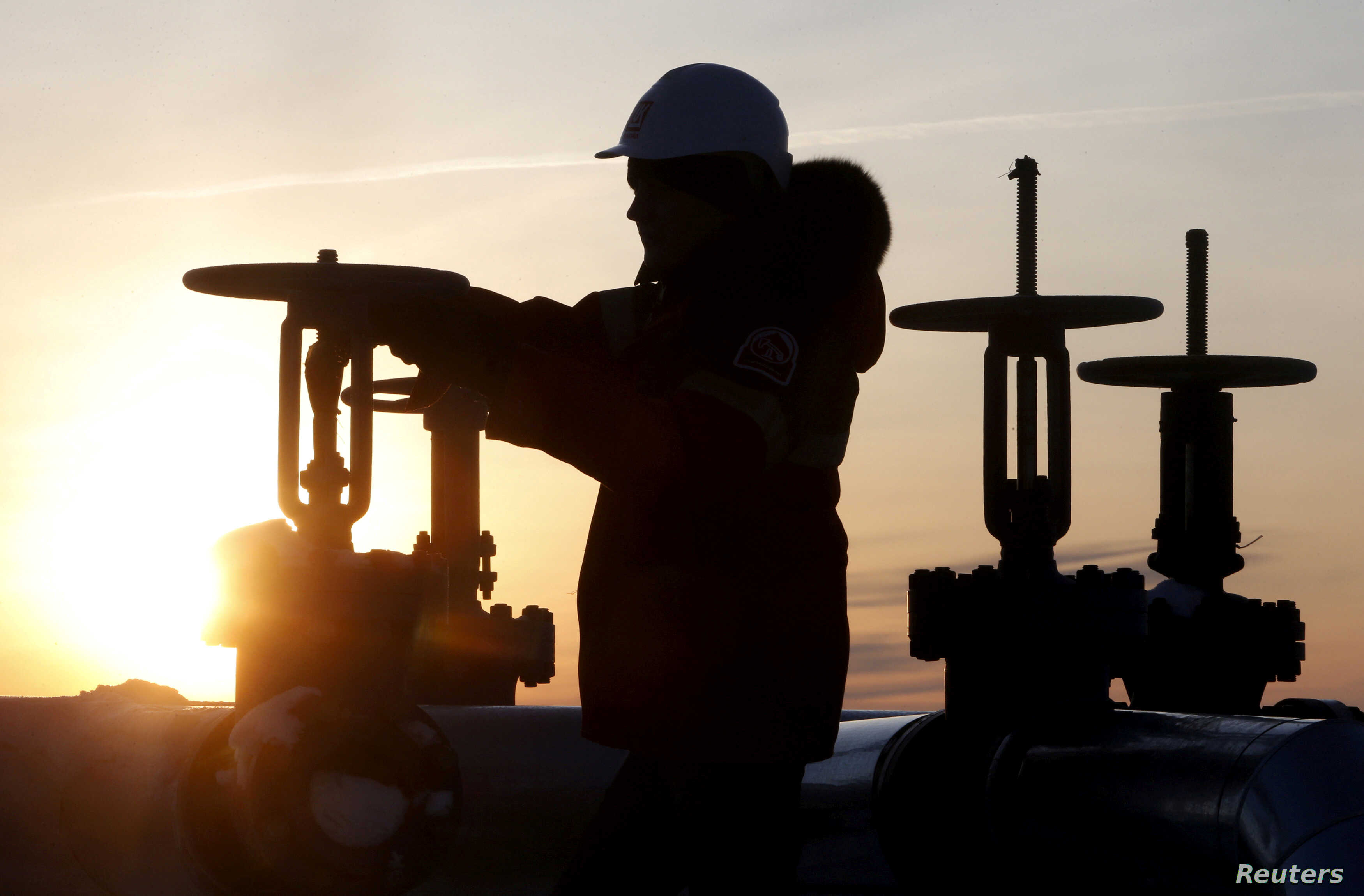 FILE - A worker checks the valve of an oil pipe outside the West Siberian city of Kogalym, Russia, Jan. 25, 2016.