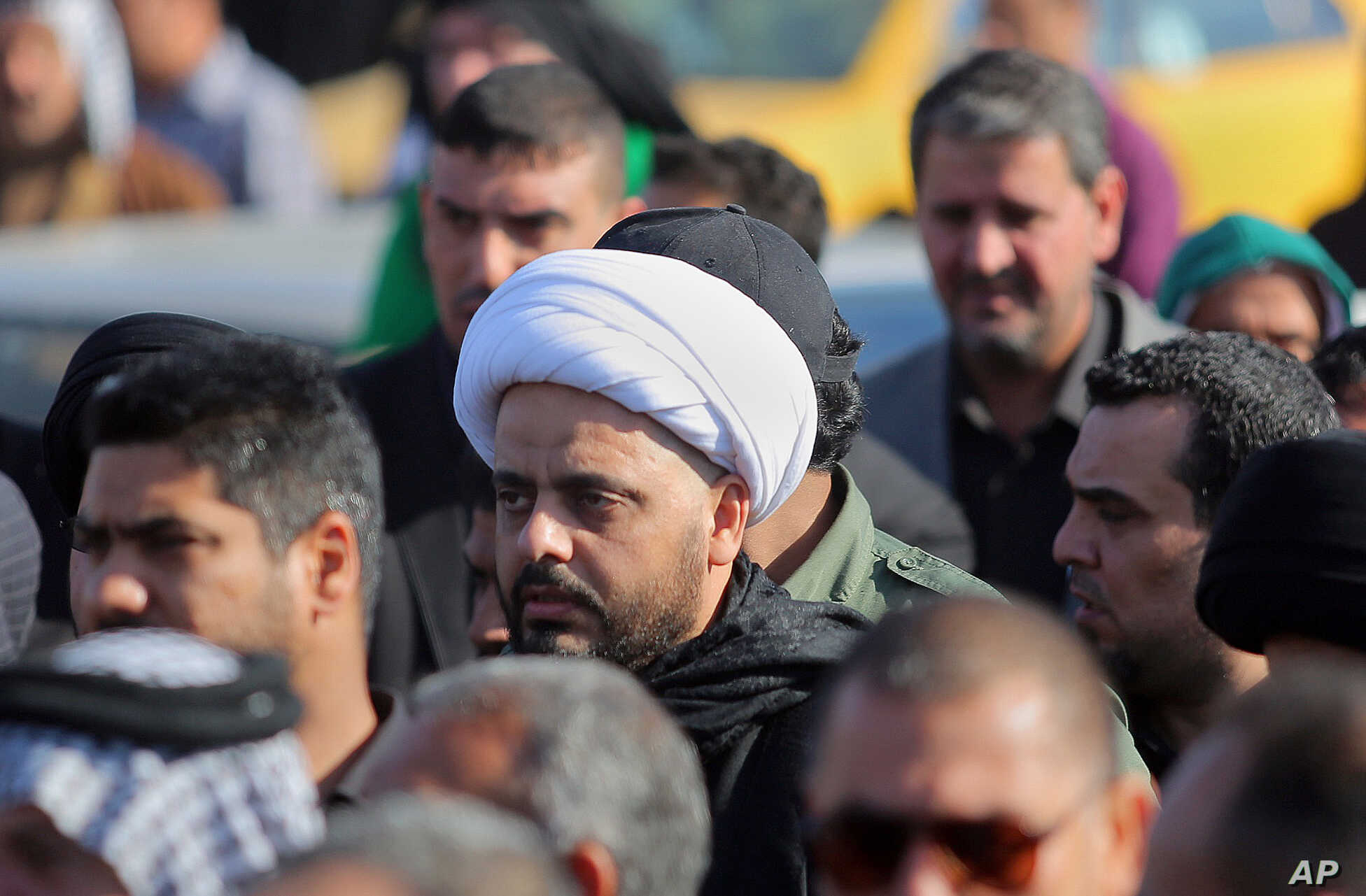 FILE - Qais al-Khazali, center, the leader of the Shi'ite group Asa'ib Ahl al-Haq, or League of the Righteous, attends funeral procession of six members  of his militia who were killed in Tikrit fighting Islamic militants, in Najaf, 100 miles (160 ki...