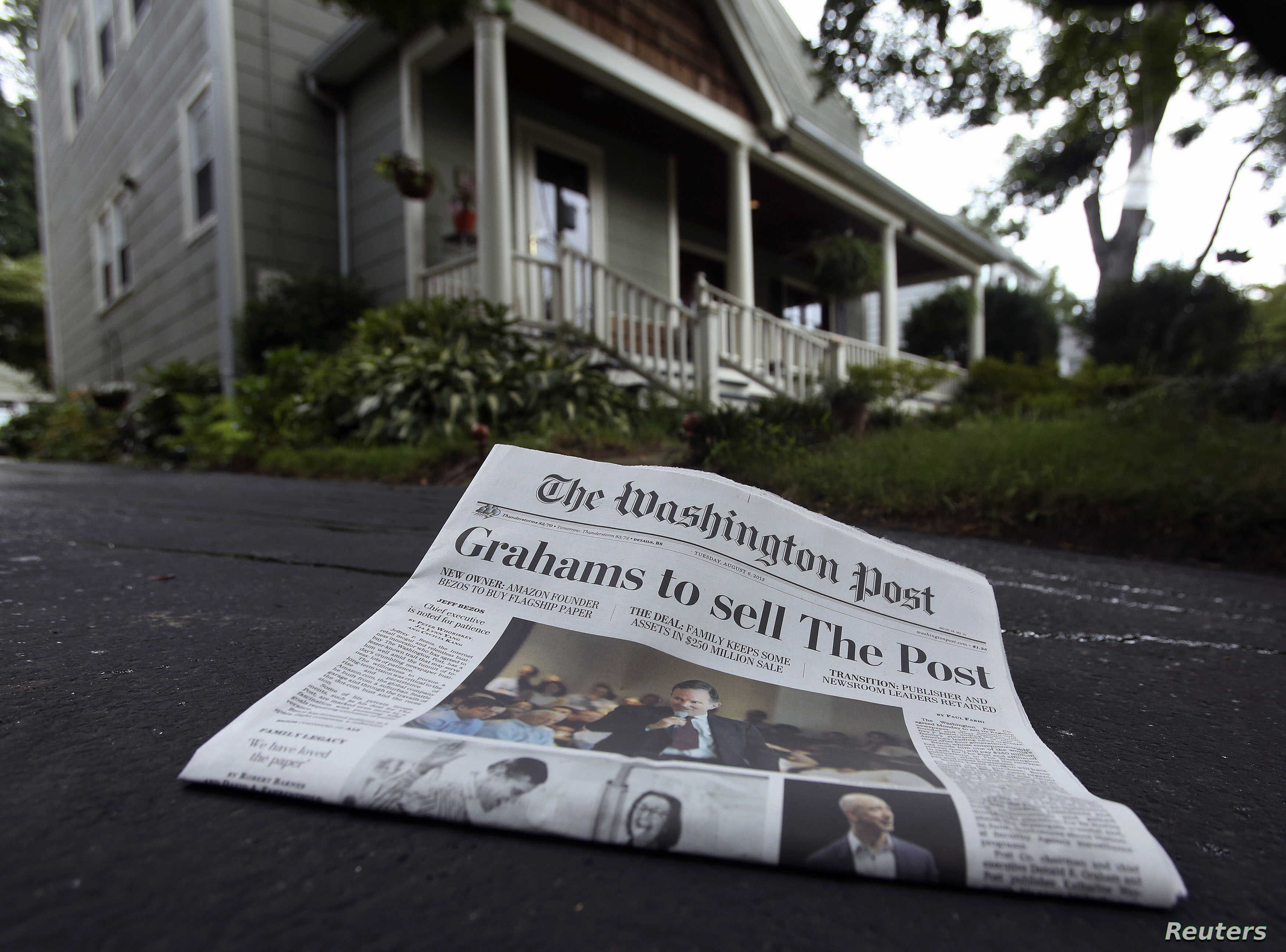 A morning edition of the Washington Post lies in a driveway after delivery in this photo illustration taken in Silver Spring, Maryland, August 6, 2013.