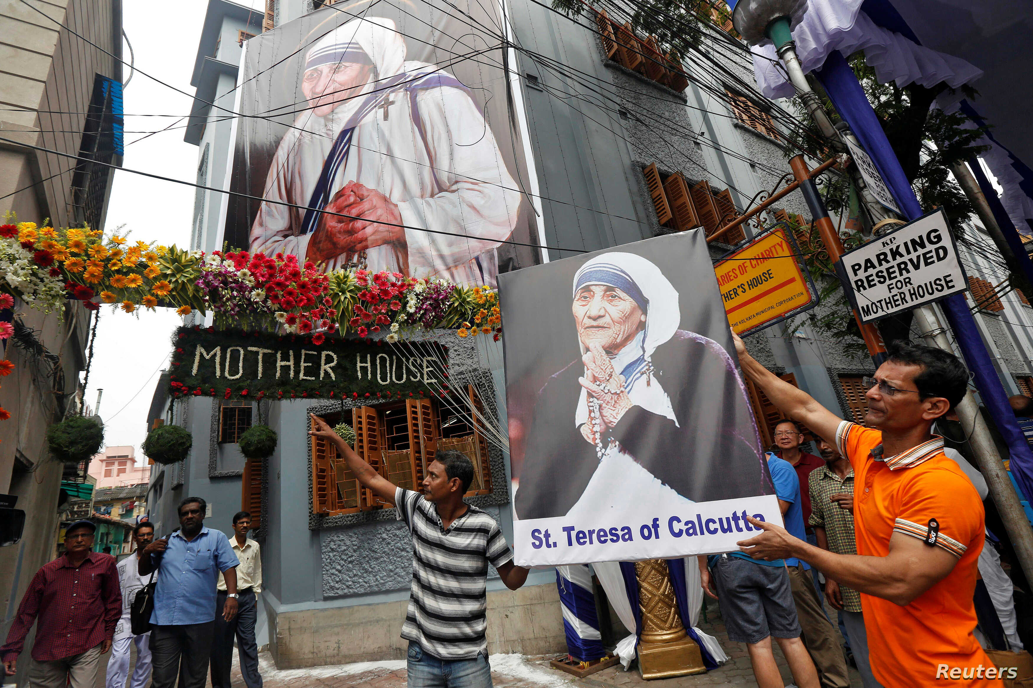 A man holds a poster of Mother Teresa outside the  Missionaries of Charity building in Kolkata as she was canonised during a ceremony held in the Vatican, India, Sept. 4, 2016.
