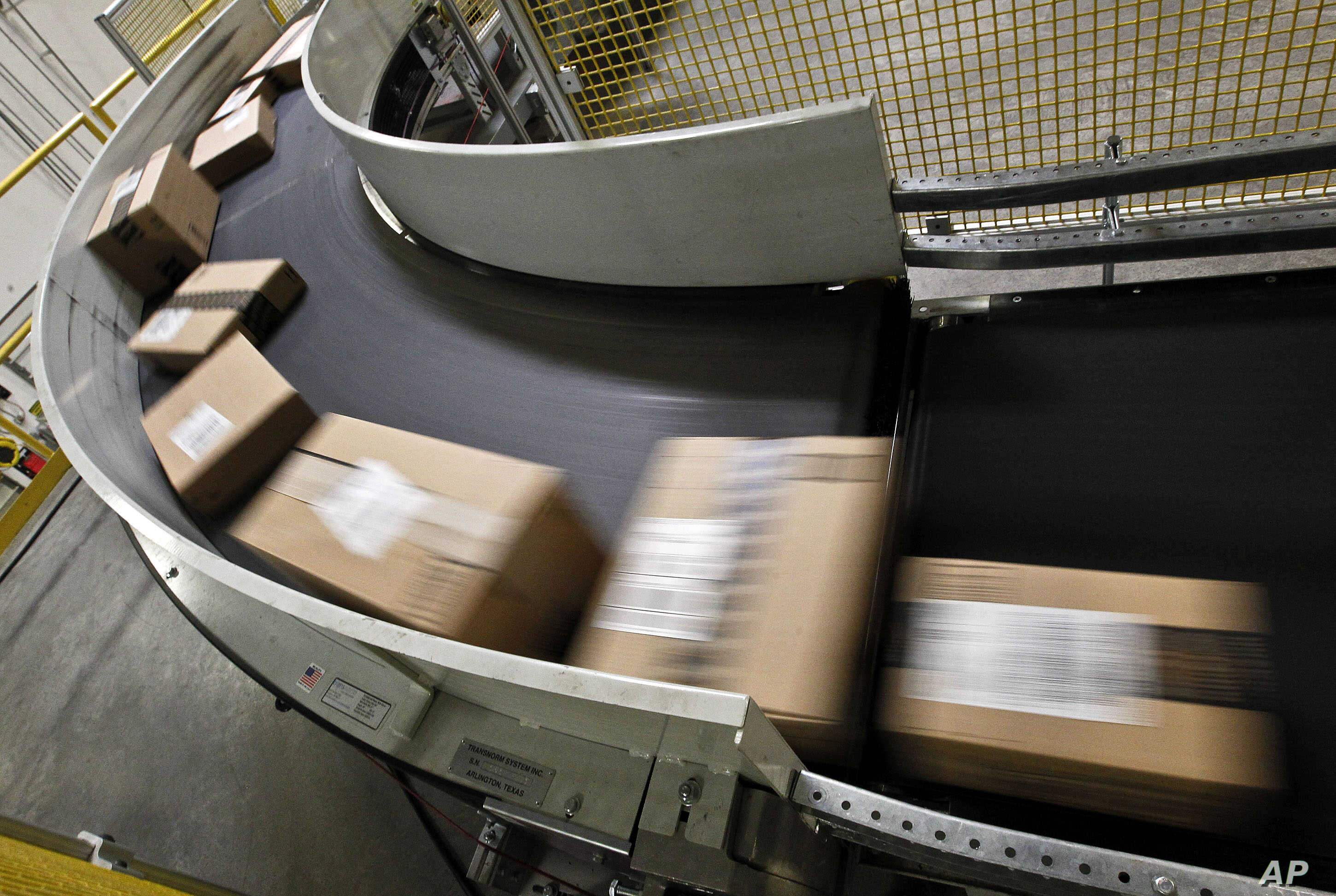FILE - Packages that are ready to ship move along a conveyor belt at the Amazon.com 1.2 million-square-foot fulfillment center in Phoenix, Arizona,  Nov. 26, 2012.