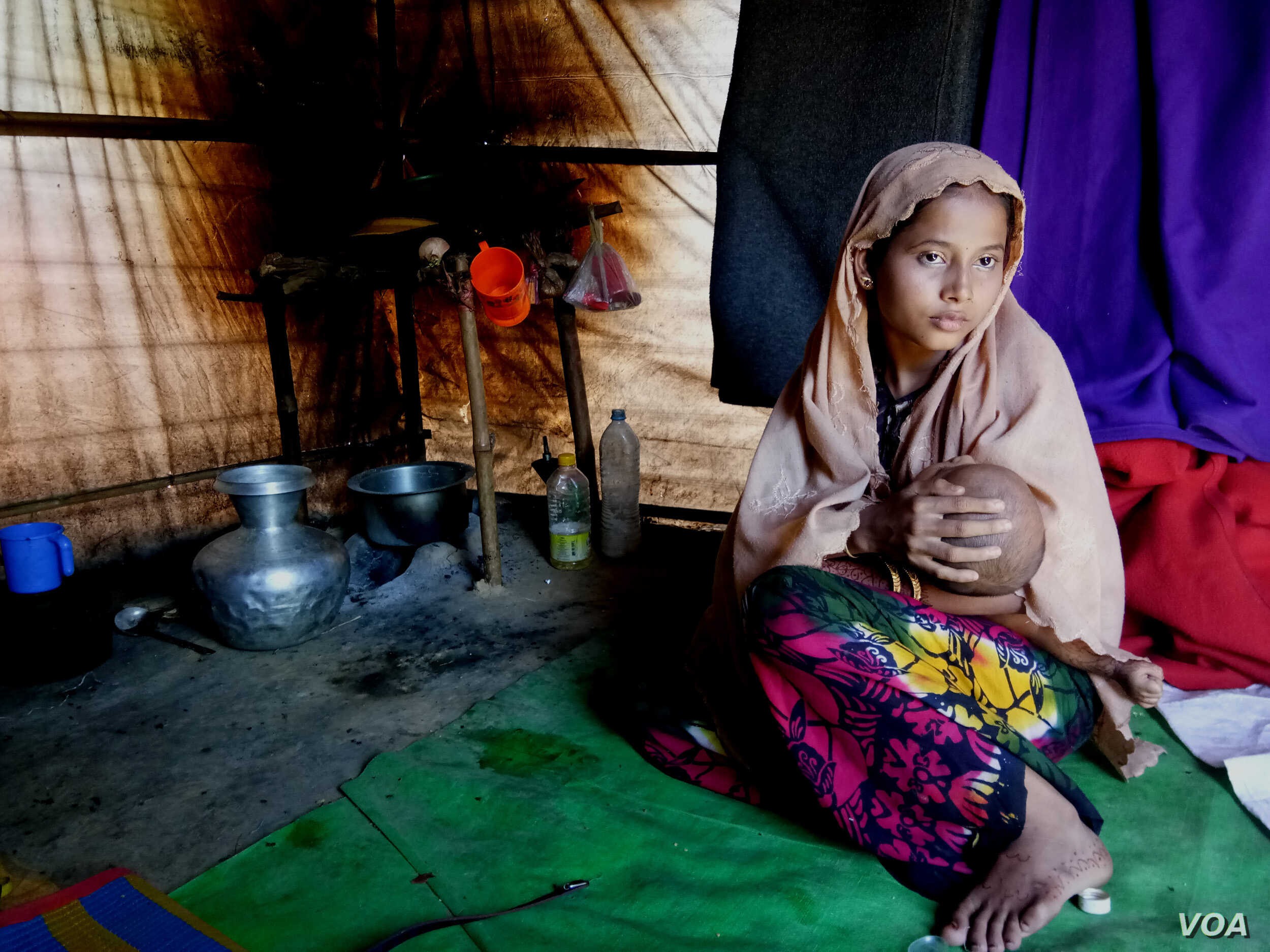 Pregnant Rohingya refugee Sitara Begum, 14, holding her 7-month-old baby, was married off in Myanmar when she was 13. (Photo by Noor Hossain)