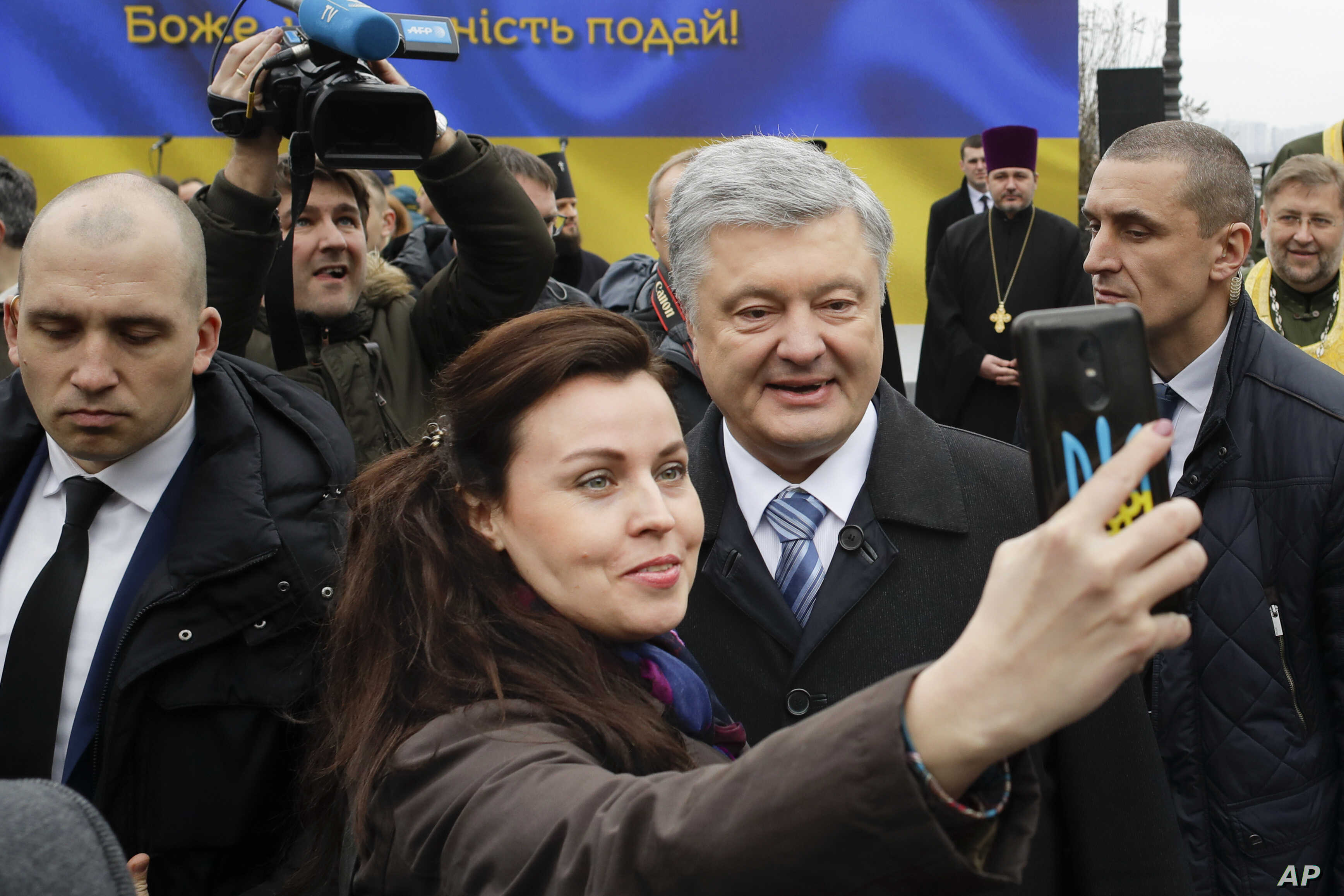 Incumbent Ukrainian President Petro Poroshenko, surrounded by bodyguards, poses for a selfie with a supporter, after a public prayer service ahead of Sunday's presidential election, in Kyiv, Ukraine, March 30, 2019.
