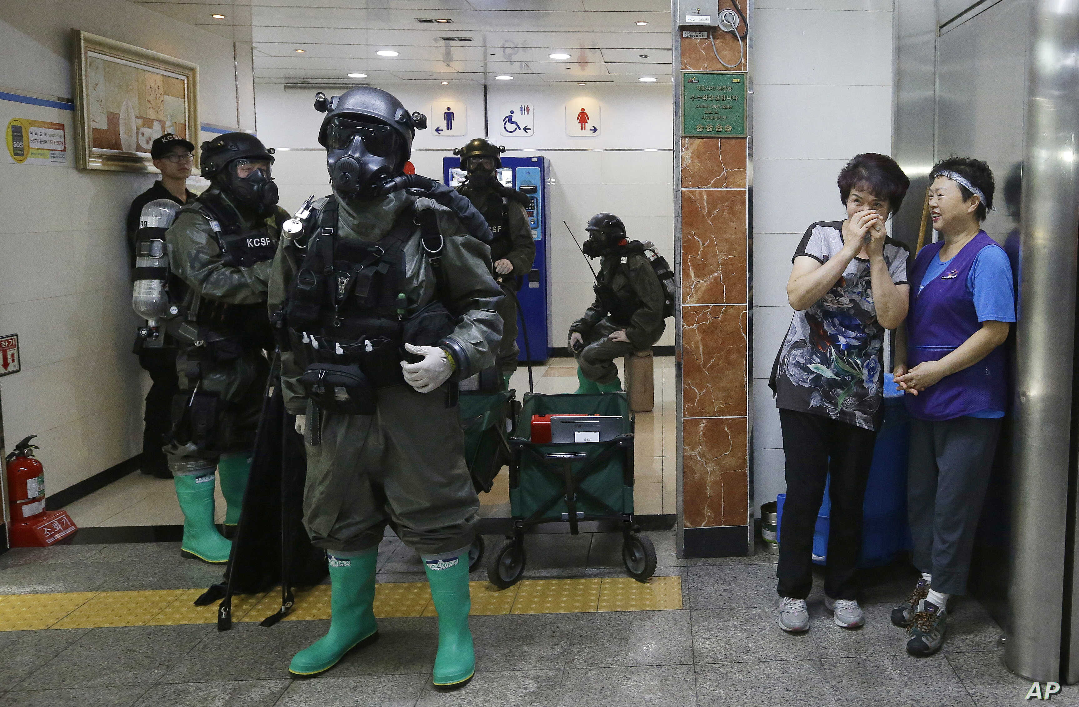 South Korean army soldiers stand as women watch during an anti-terror drill as part of the Ulchi Freedom Guardian exercise, at Yoido Subway Station in Seoul, South Korea, Aug. 23, 2016.