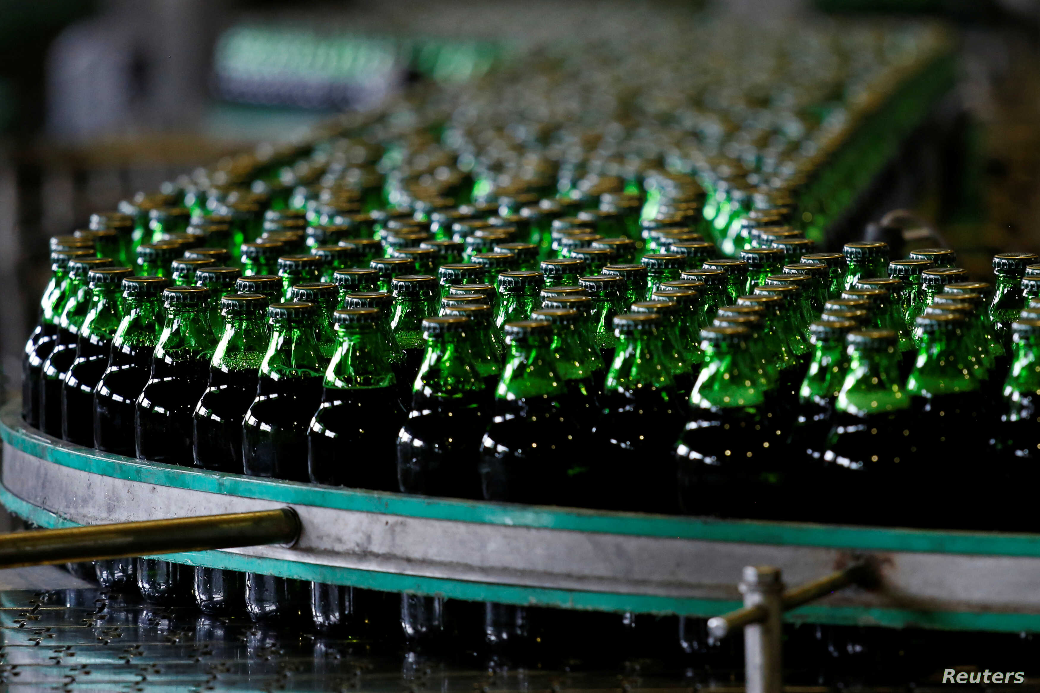 FILE - Bottles of beer move along a production line at a factory of Saigon Beer Corporation (Sabeco) in Hanoi, Vietnam, June 23, 2017.