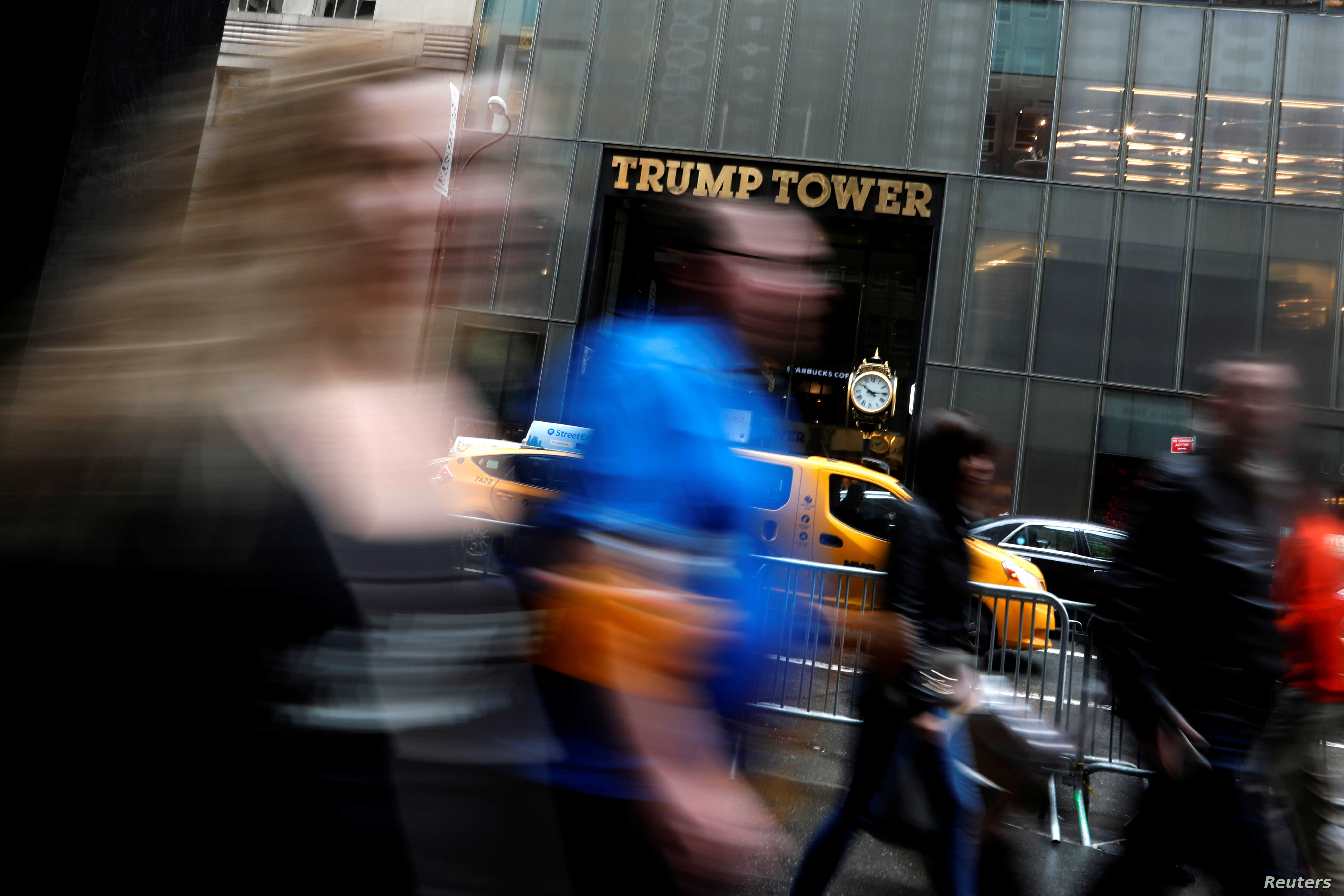 FILE - FILE - Pedestrians are seen in a slow shutter speed photograph as they pass Trump Tower on 5th Avenue in New York City, April 26, 2017.