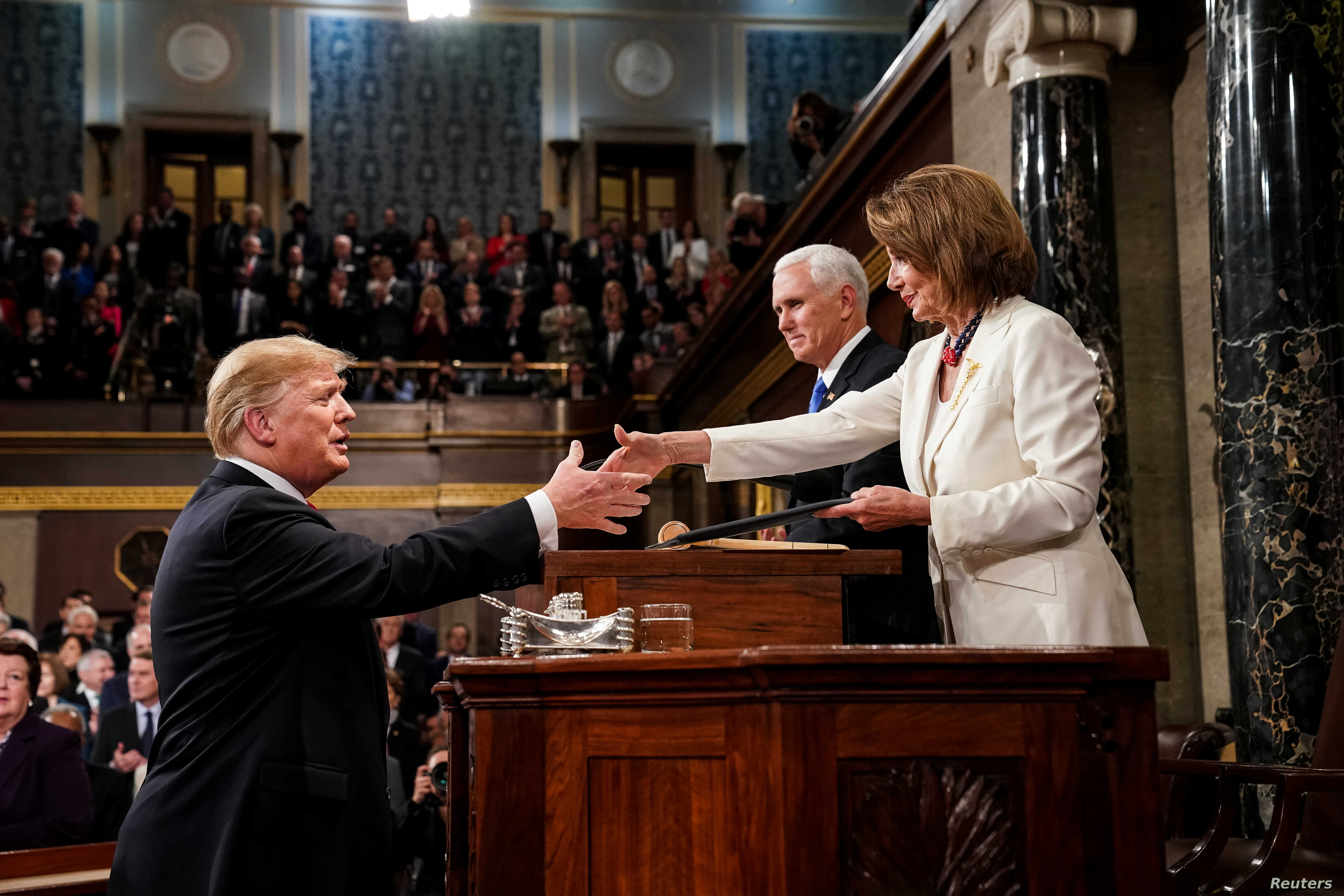 President Donald Trump, before delivering the State of the Union address, shakes the hand of Speaker of the House Nancy Pelosi. Vice President Mike Pence, center, is also in attendance at the Capitol in Washington, February 5, 2019.