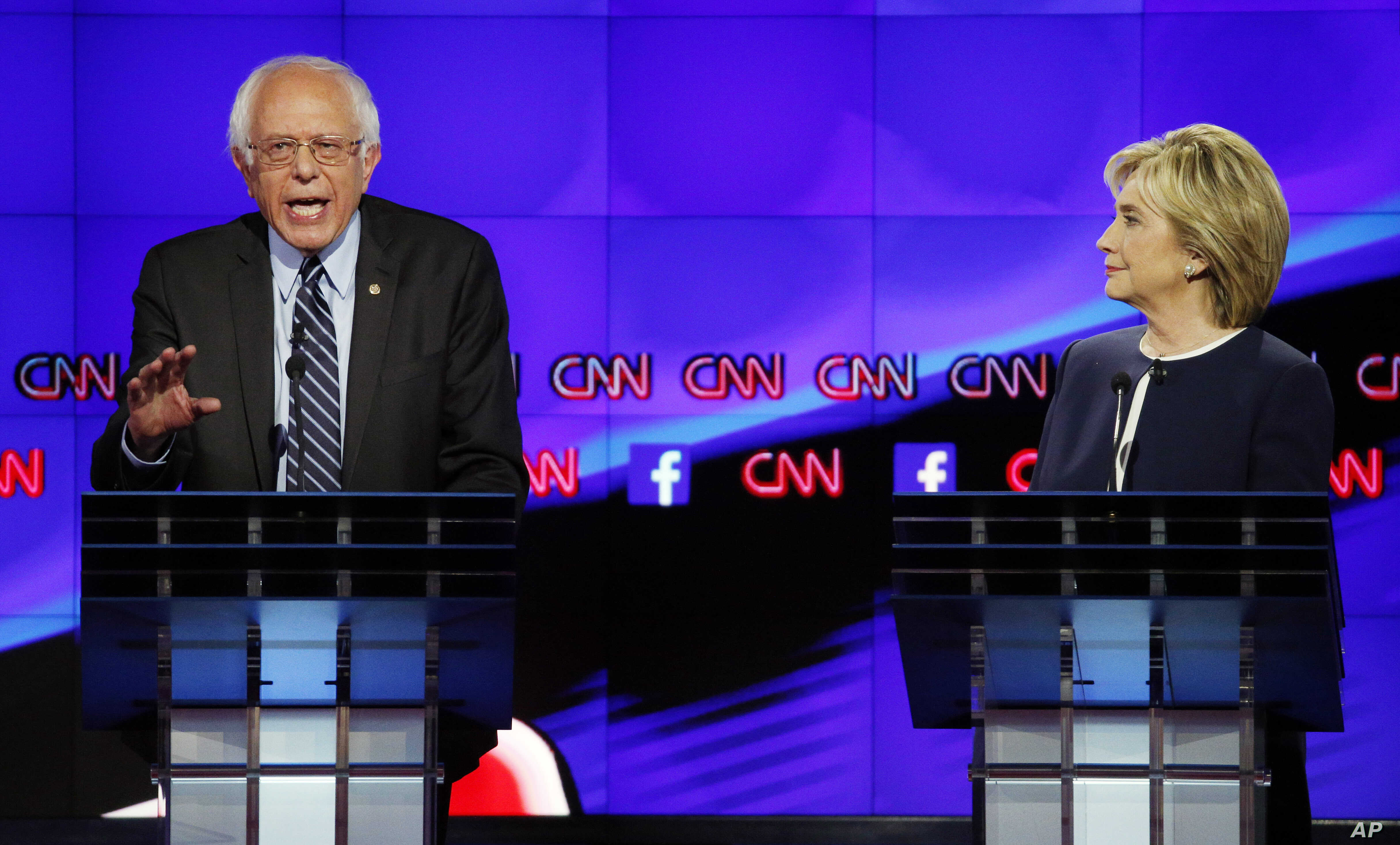 Hillary Rodham Clinton listens as Sen. Bernie Sanders, of Vermont, speaks during the CNN Democratic presidential debate in Las Vegas, Oct. 13, 2015.