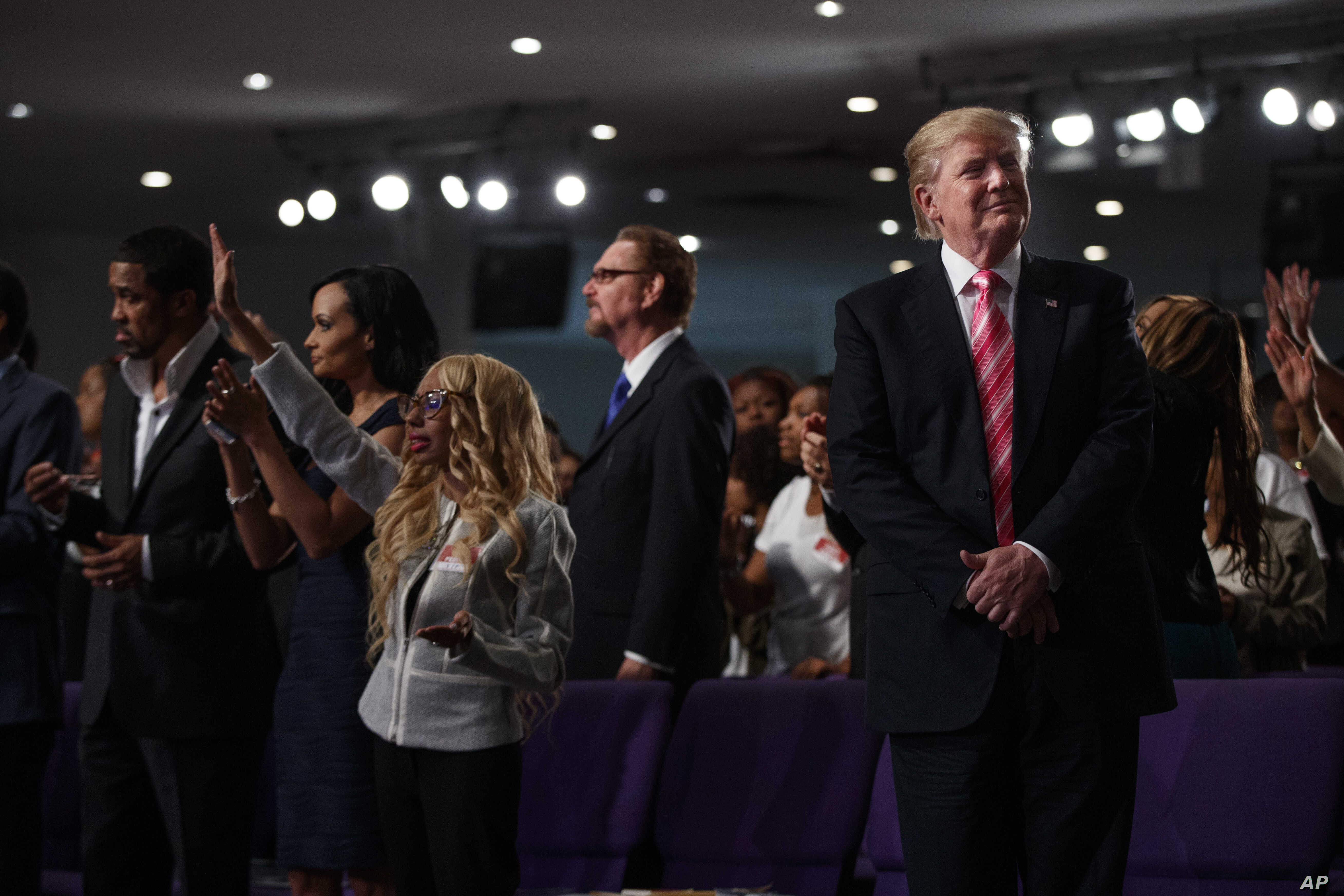 Republican presidential candidate Donald Trump, right, looks on during a church service at Great Faith Ministries in Detroit, Sept. 3, 2016.