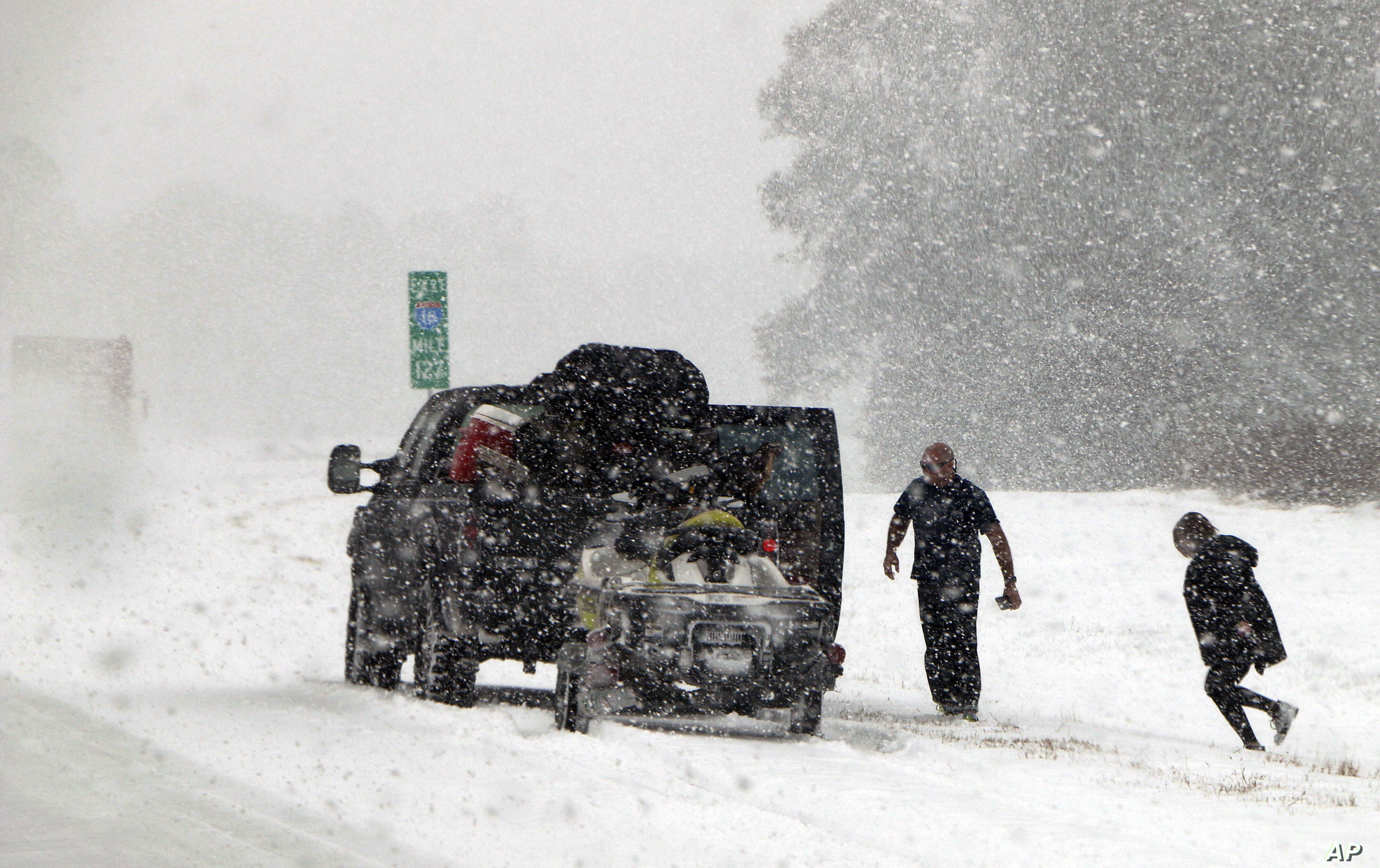 People attend to their vehicle on Interstate 26, near Savannah, Ga., Jan. 3, 2018. A brutal winter storm dumped snow in Tallahassee, Fla., Wednesday for the first time in nearly three decades before slogging up the Atlantic coast.