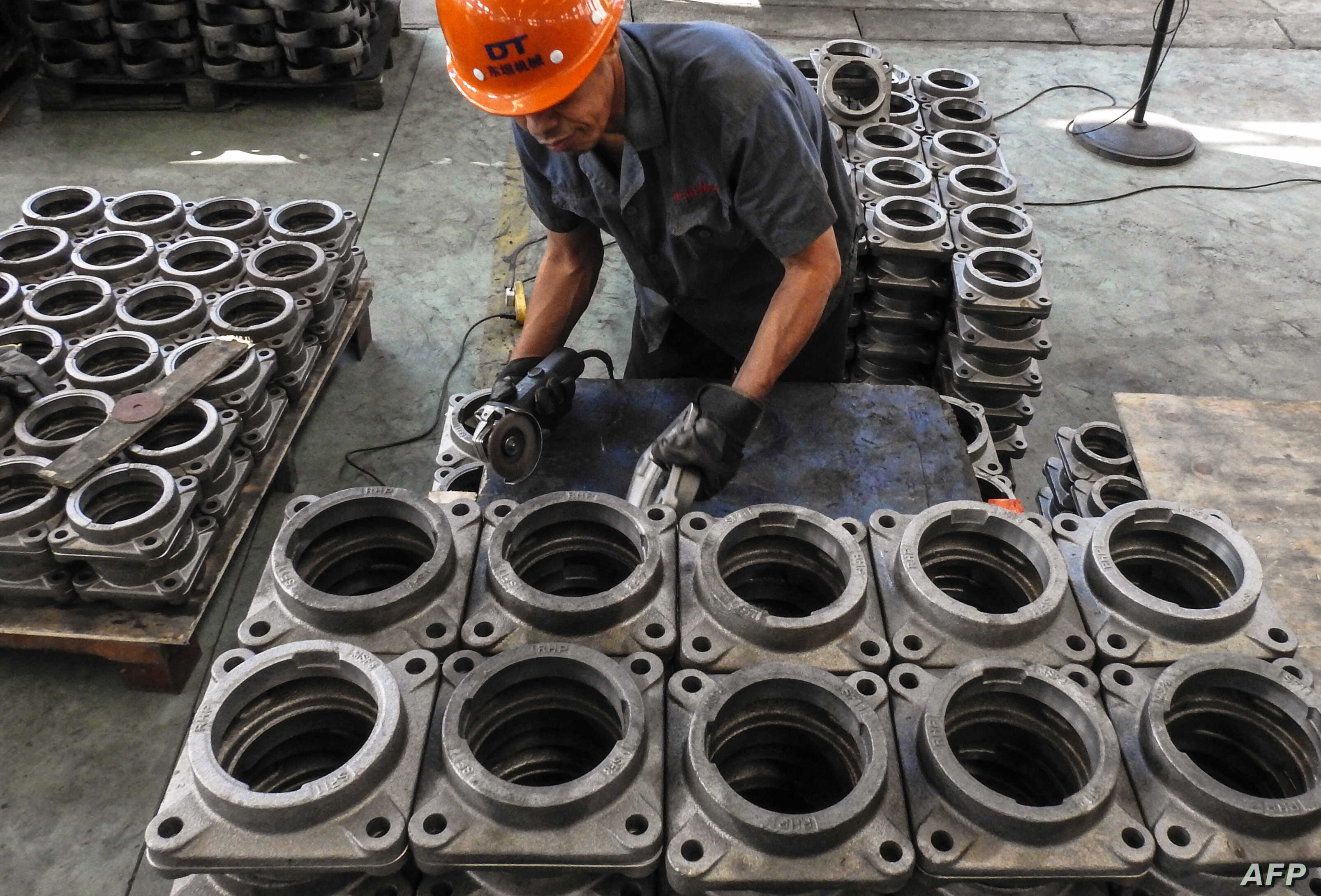An employee works on transmission parts at a factory in Lianyungang in China's eastern Jiangsu province, Sept. 14, 2018. The Chinese economy revealed fresh signs of softness, with data showing the pace of investment slowing to record lows while retai...