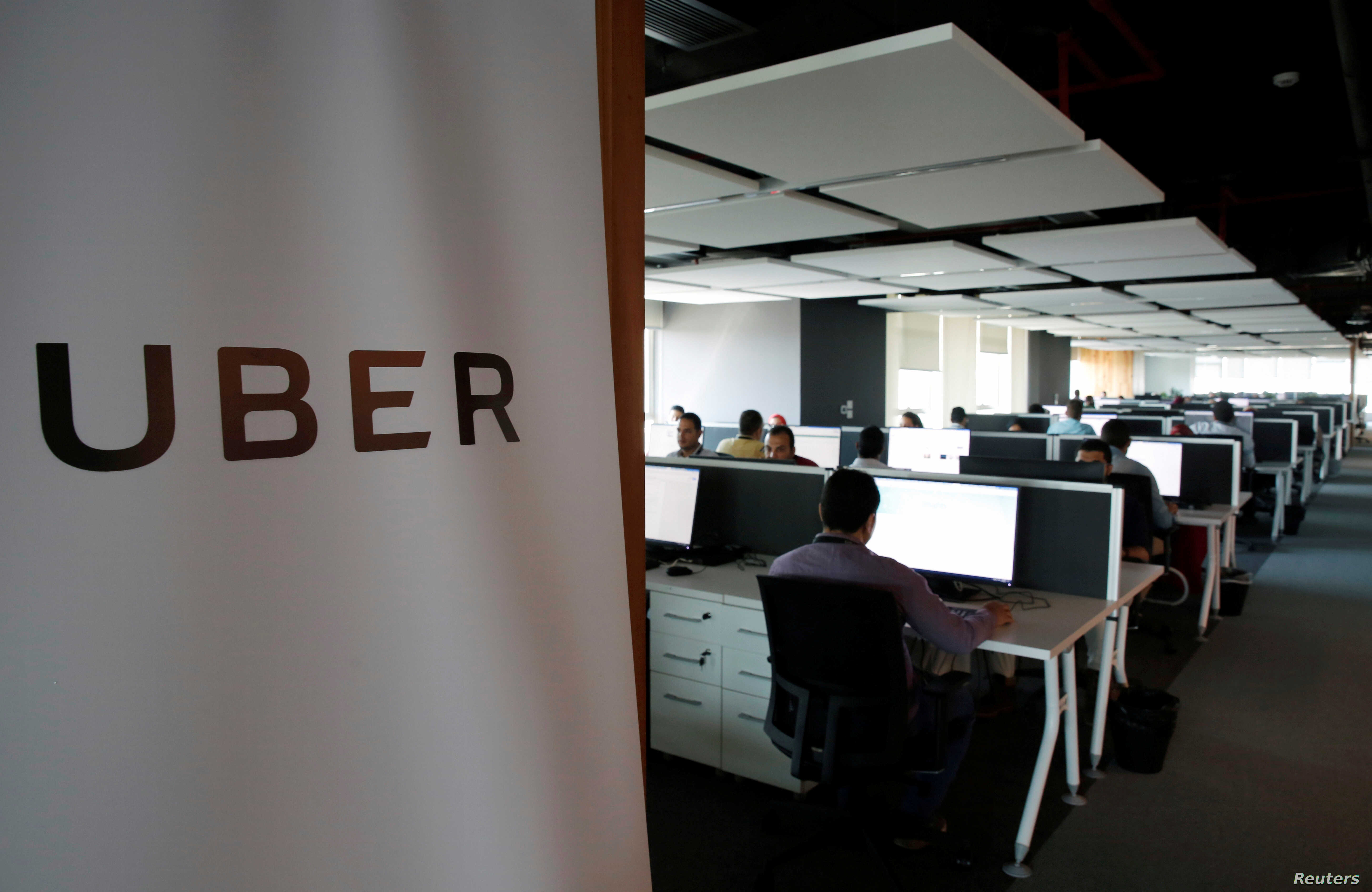 FILE - Employees work inside Uber's Center of Excellence office in Cairo, Egypt, Oct. 10, 2017.