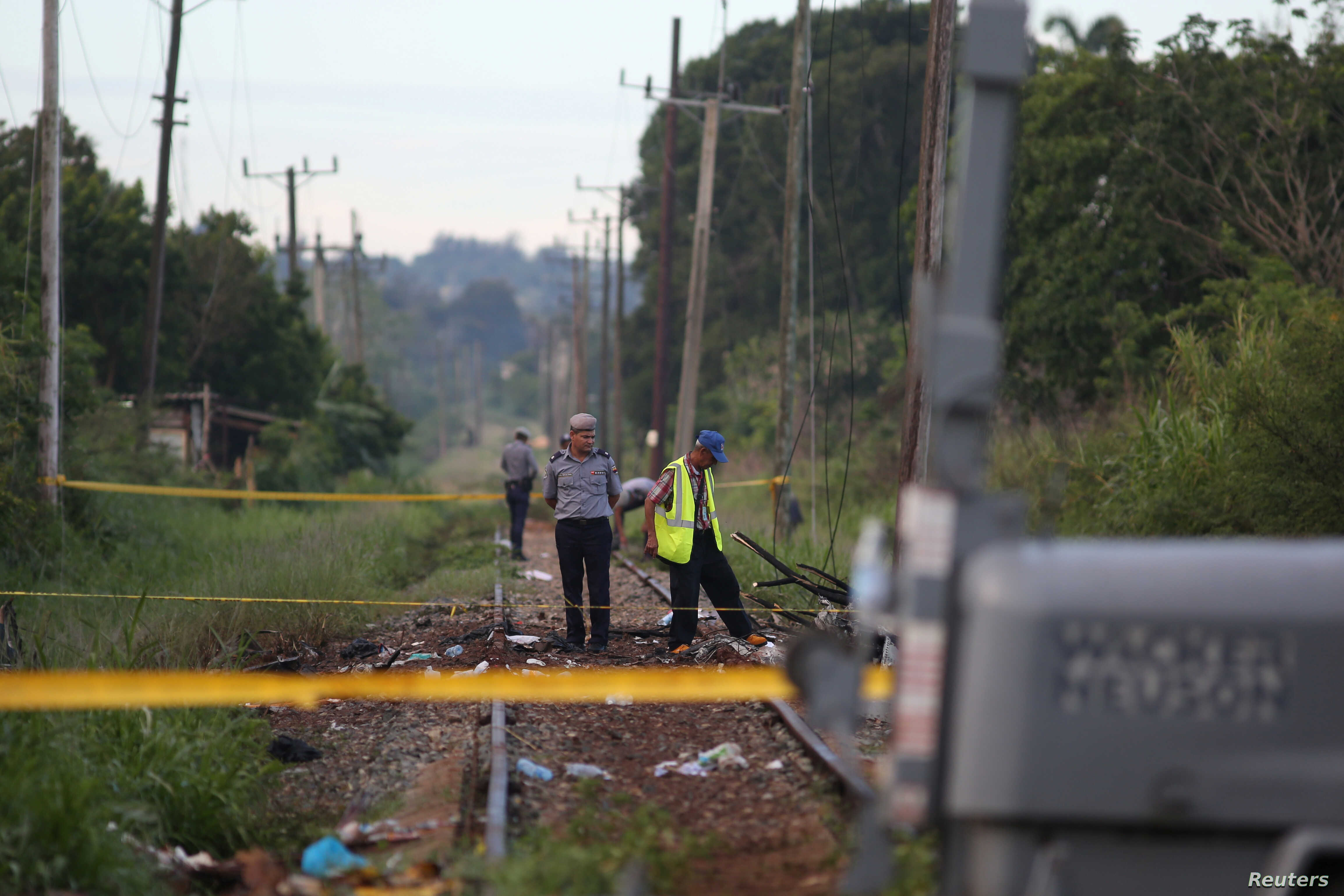 Police officers stand at the site where a Boeing 737 plane crashed after taking off from Havana's main airport the previous day, in the agricultural area of Boyeros, Cuba, May 19, 2018.