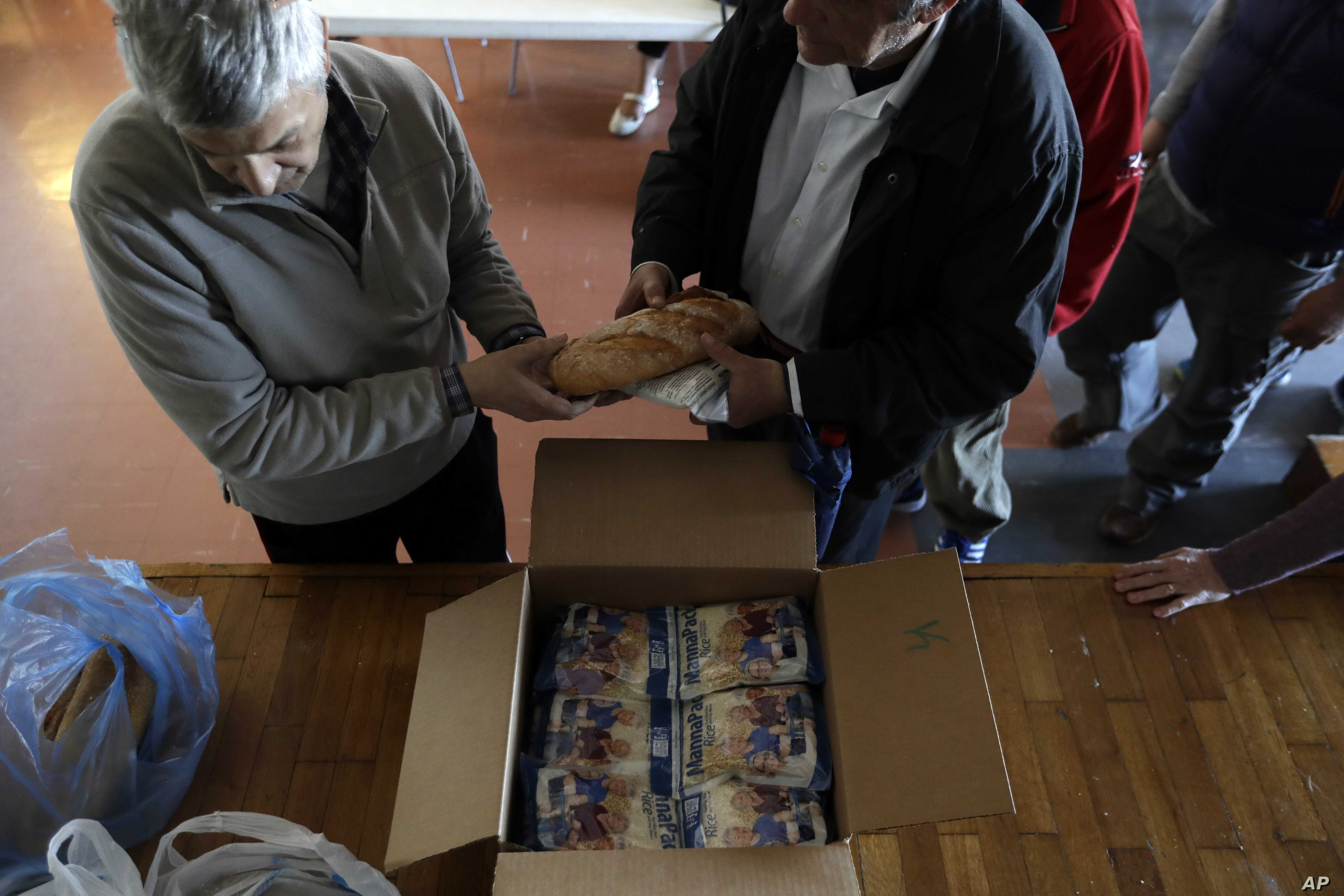 A volunteer delivers bread and other supplies to homeless persons at the ''Shelter of Love and Solidarity'' in central Athens, April 25, 2017.