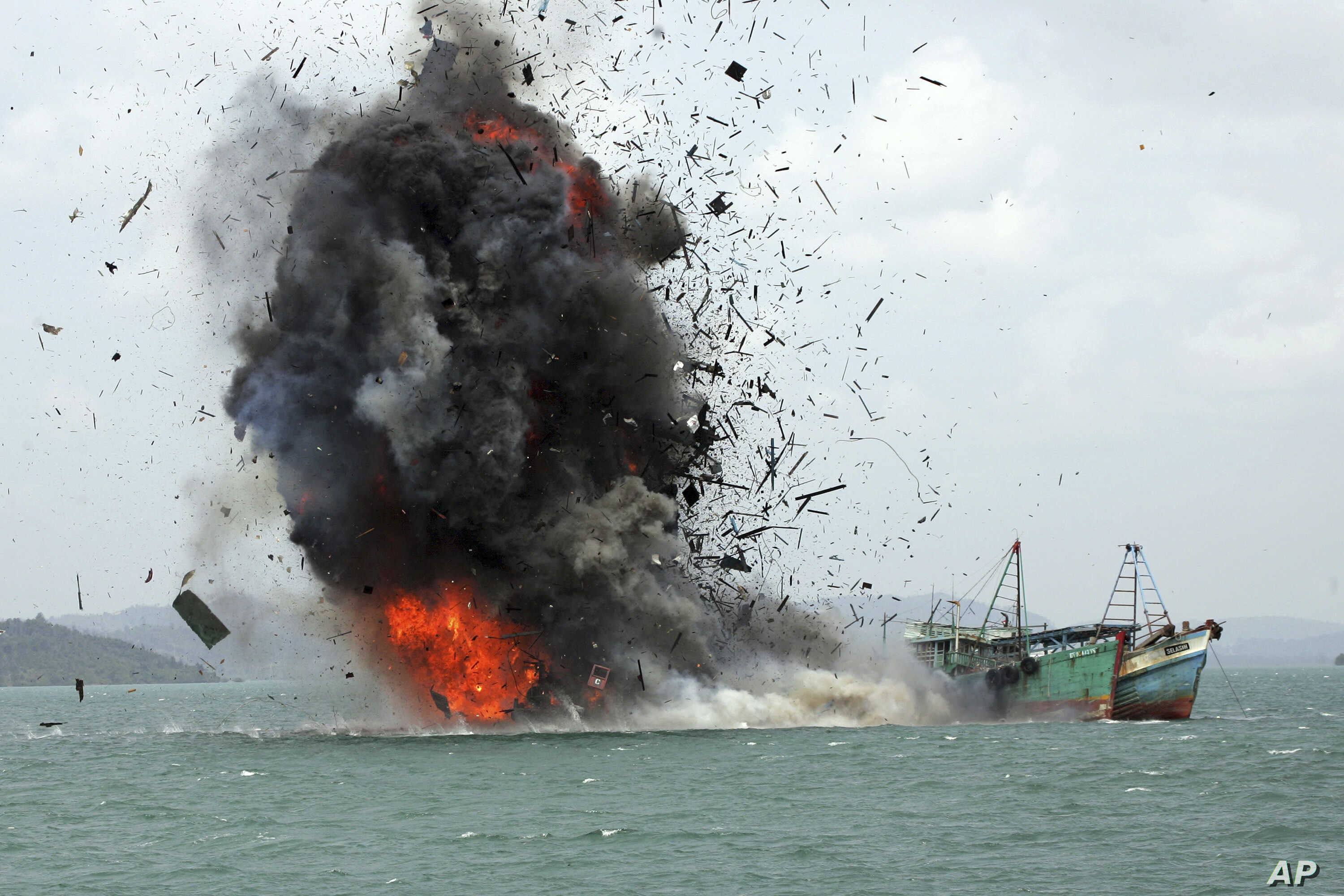 FILE - Debris flies into the air as foreign fishing boats are blown up, Feb. 22, 2016, by the Indonesian Navy off Batam Island, Indonesia.
