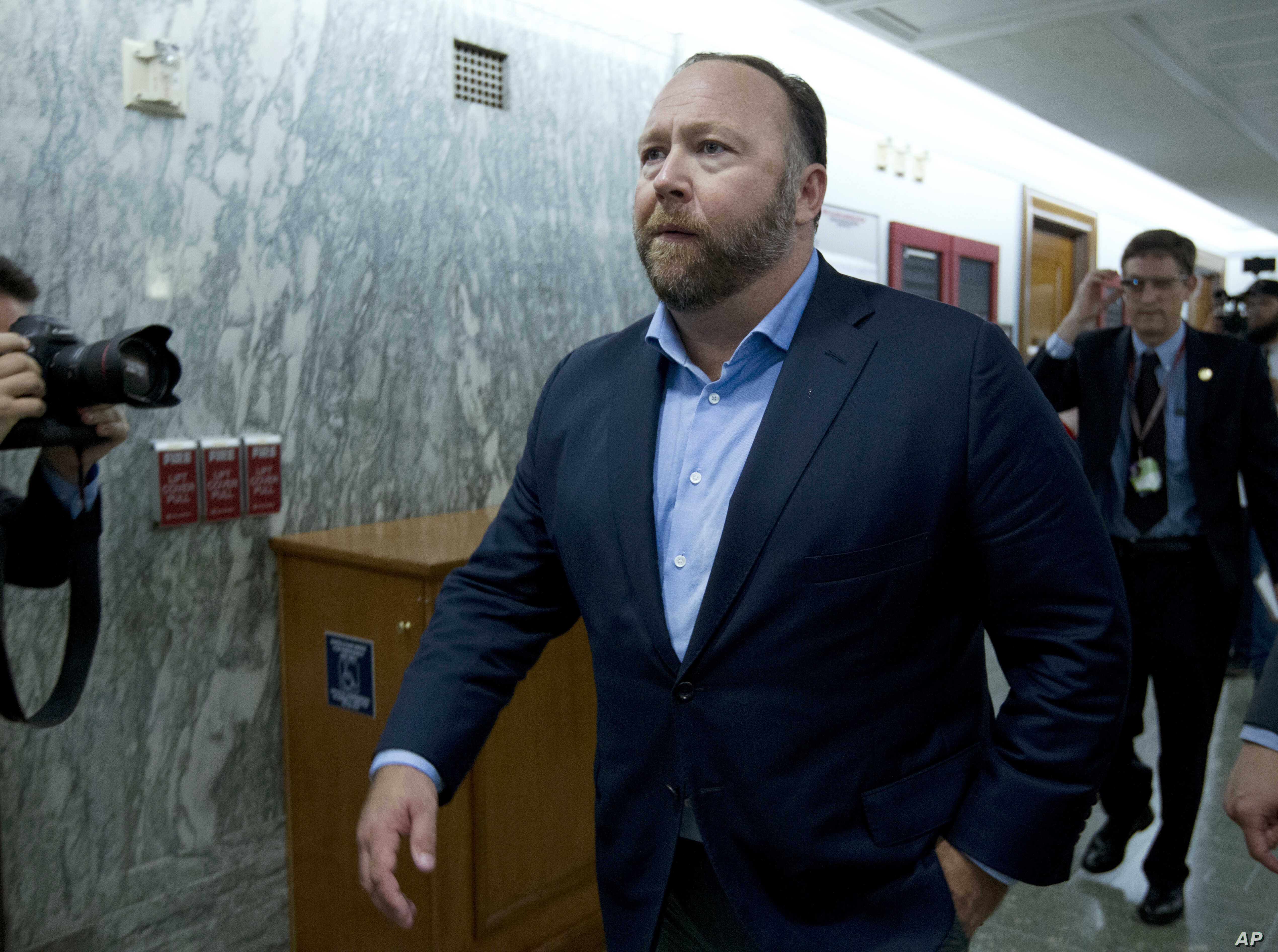 FILE -   Alex Jones, the right-wing conspiracy theorist, walks the corridors of Capitol Hill after listening to testimony on Capitol Hill in Washington, Sept. 5, 2018.