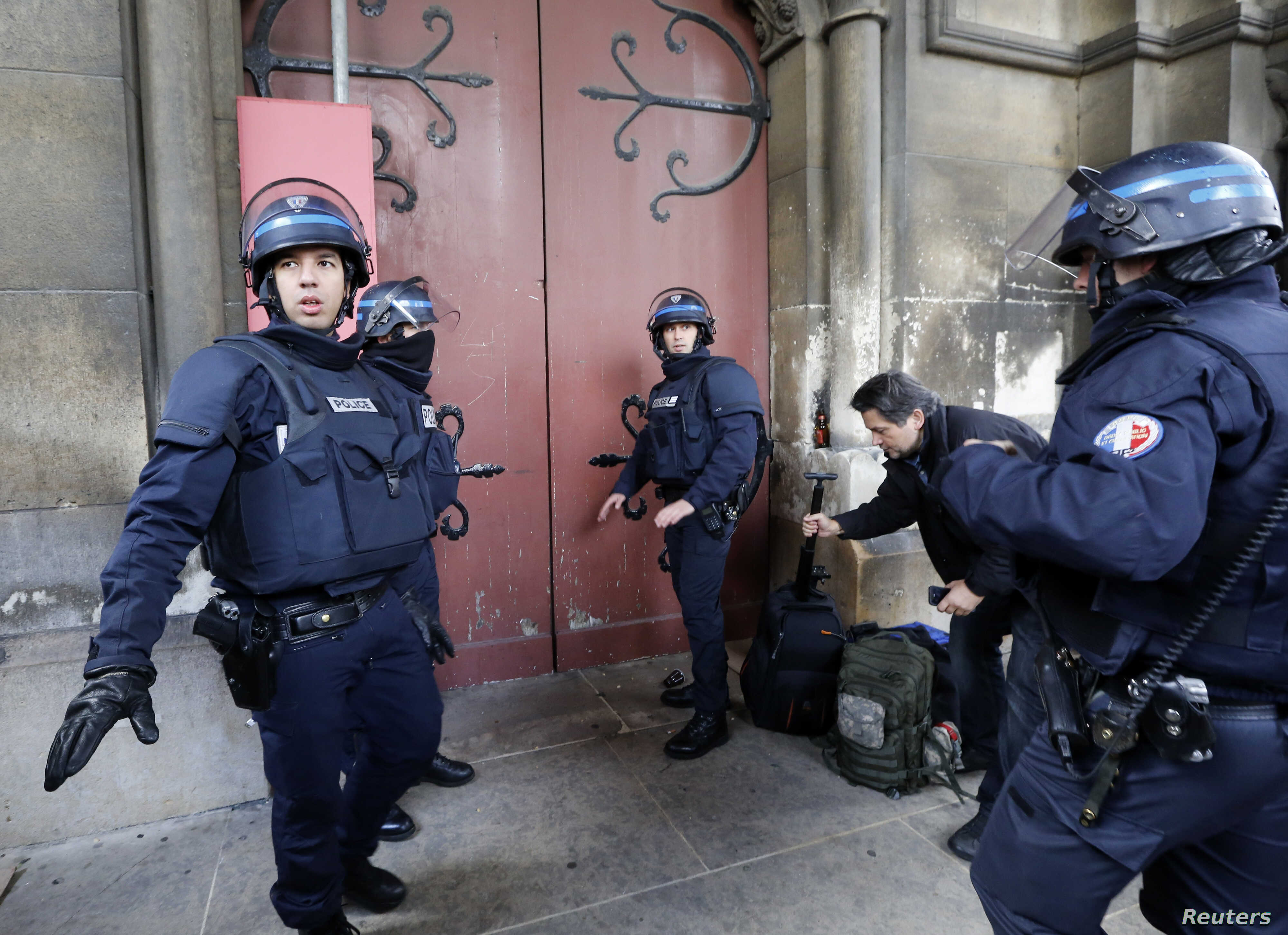 French police stand at the door of the Eglise Neuve church as they secure the area during an operation in Saint-Denis, near Paris, to catch fugitives from Friday night's deadly attacks in Paris, Nov. 18, 2015.