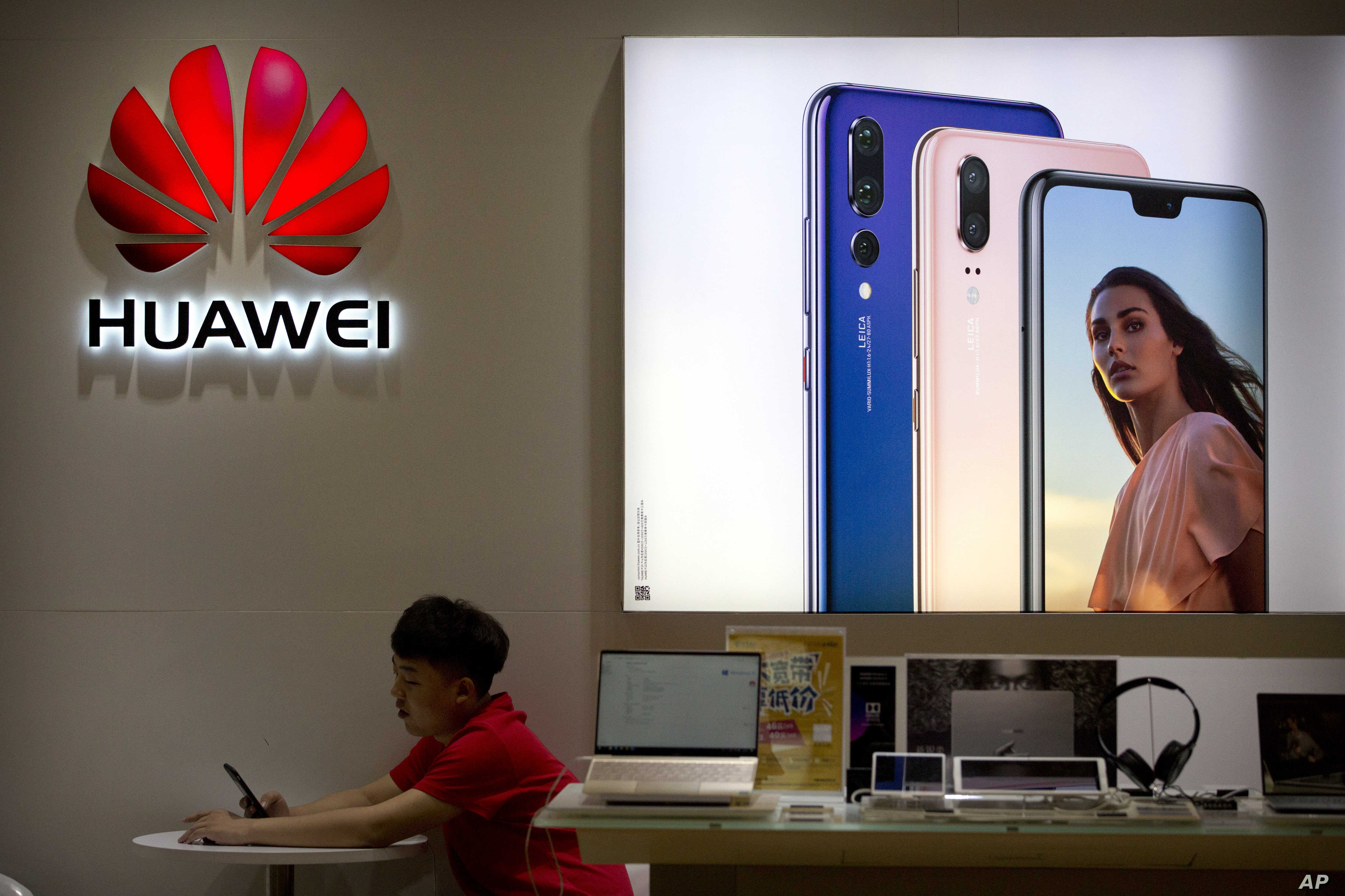 A sales clerk looks at his smartphone in a Huawei store at a shopping mall in Beijing Wednesday, July 4, 2018.