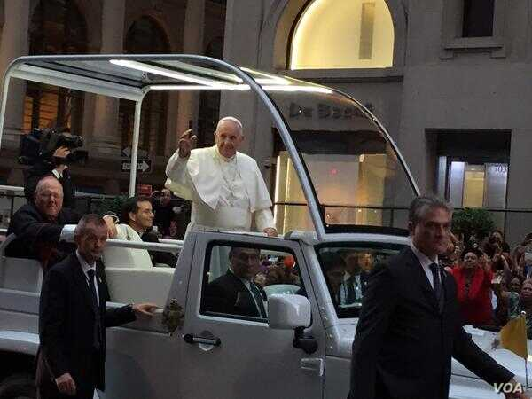 Pope Francis waves to huge crowds gathered in Manhattan as his motorcade drives along Fifth Avenue in New York, Sept. 24, 2015. (C. Presutti / VOA)