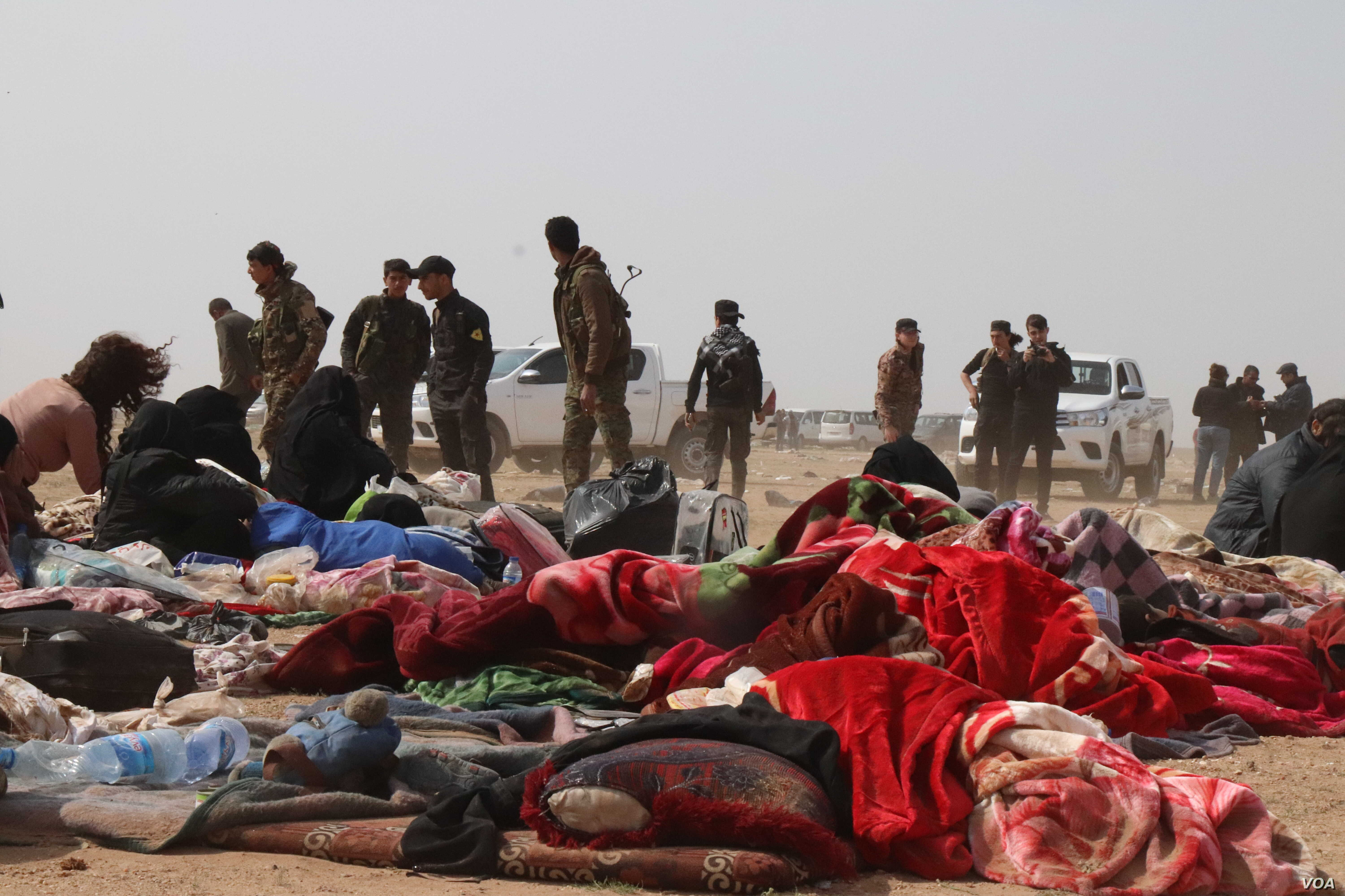 Internationally backed Syrian soldiers escort women from the war zones to refugee camps, stopping at transit centers like this one to be checked for weapons. Men are investigated more thoroughly near Baghuz in Deir el-Zour, Syria, Feb. 26, 2019. (H.M...