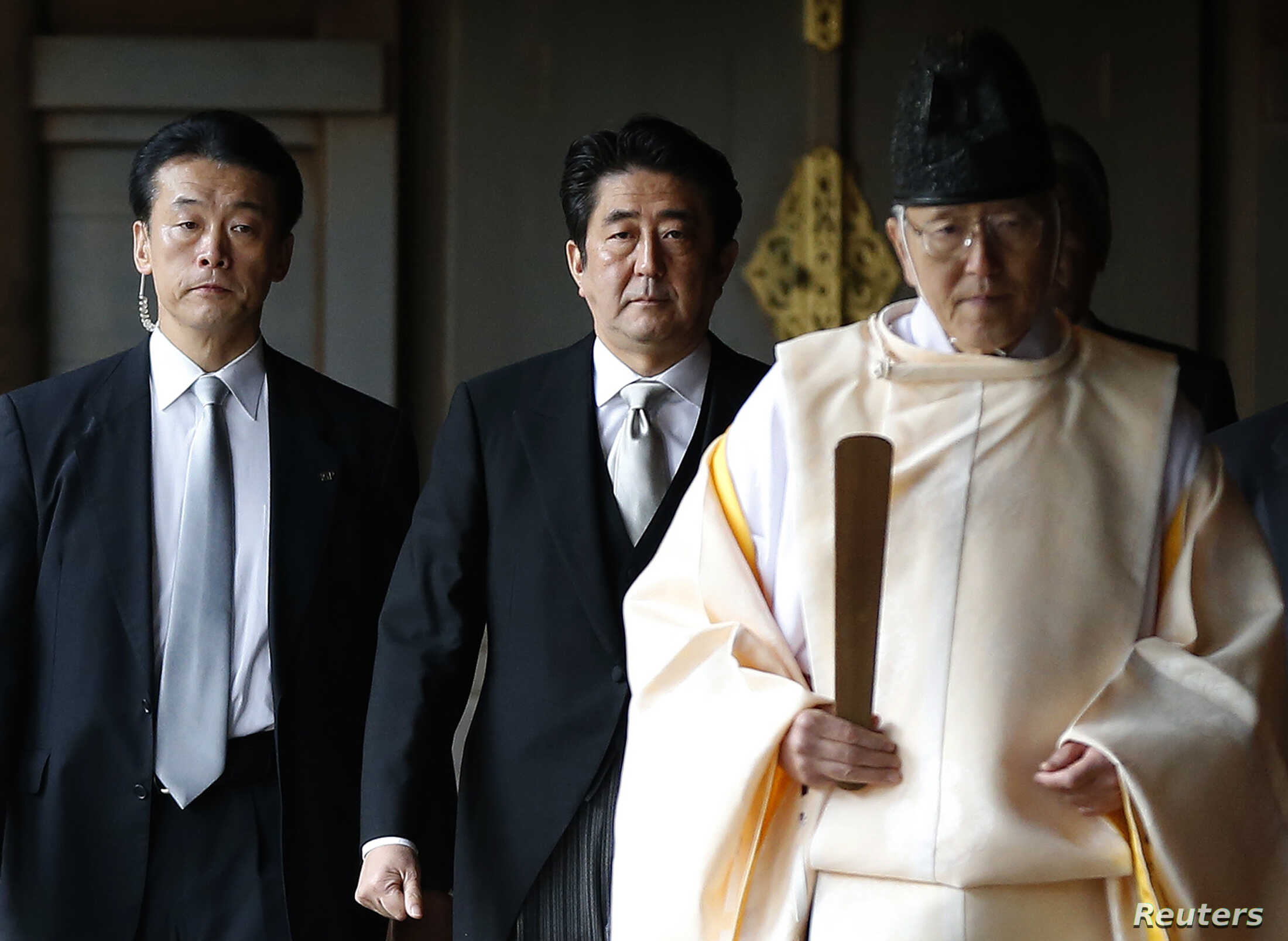 Japan's Prime Minister Shinzo Abe is led by a Shinto priest as he visits Yasukuni shrine in Tokyo, Dec. 26, 2013.