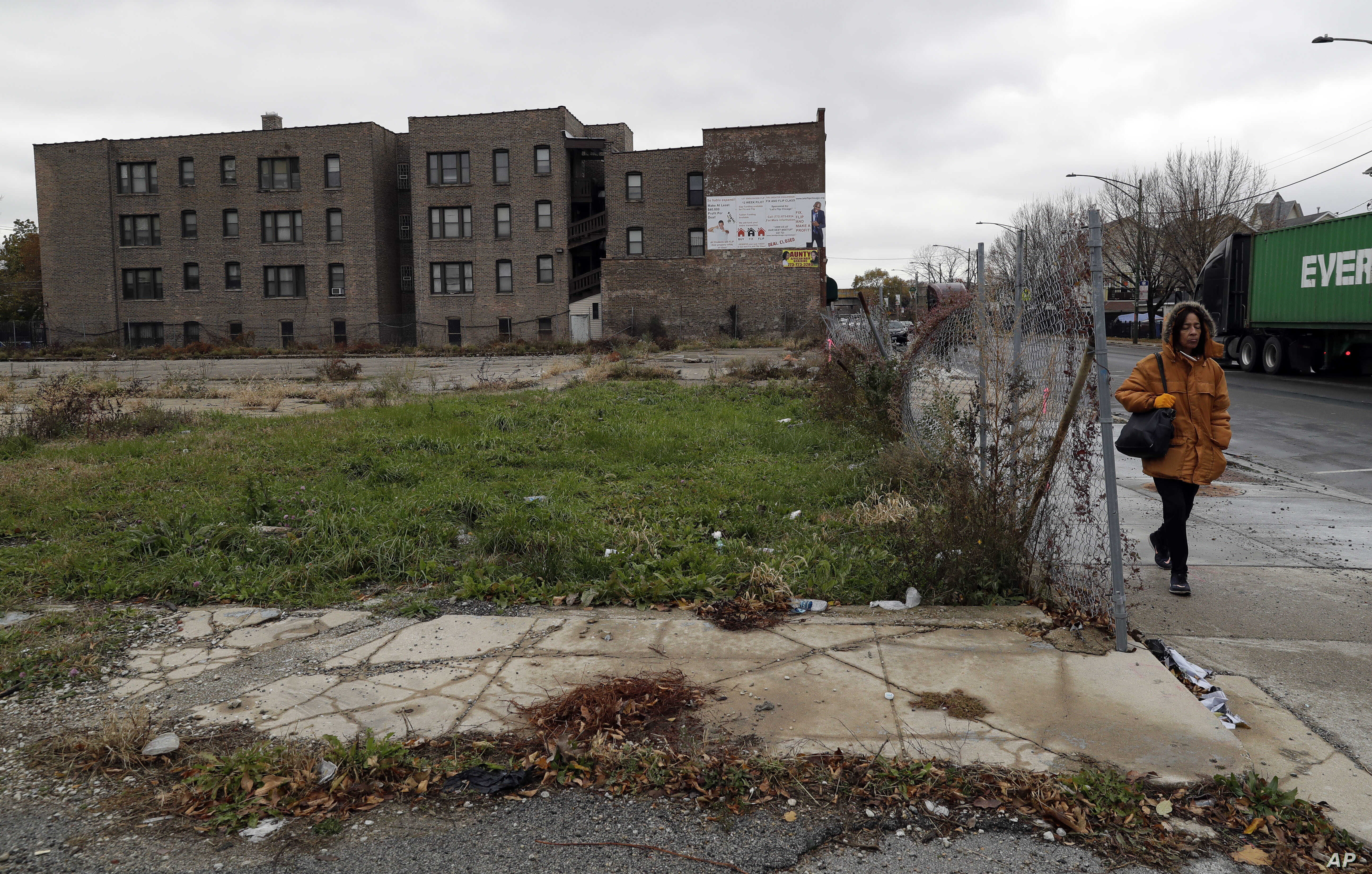 A pedestrian walks past an abandoned lot on a street on the South Side of Chicago that is part of the 6th Police District. Officers there marked a milestone this fall when they recovered their 1,000th gun for the year.