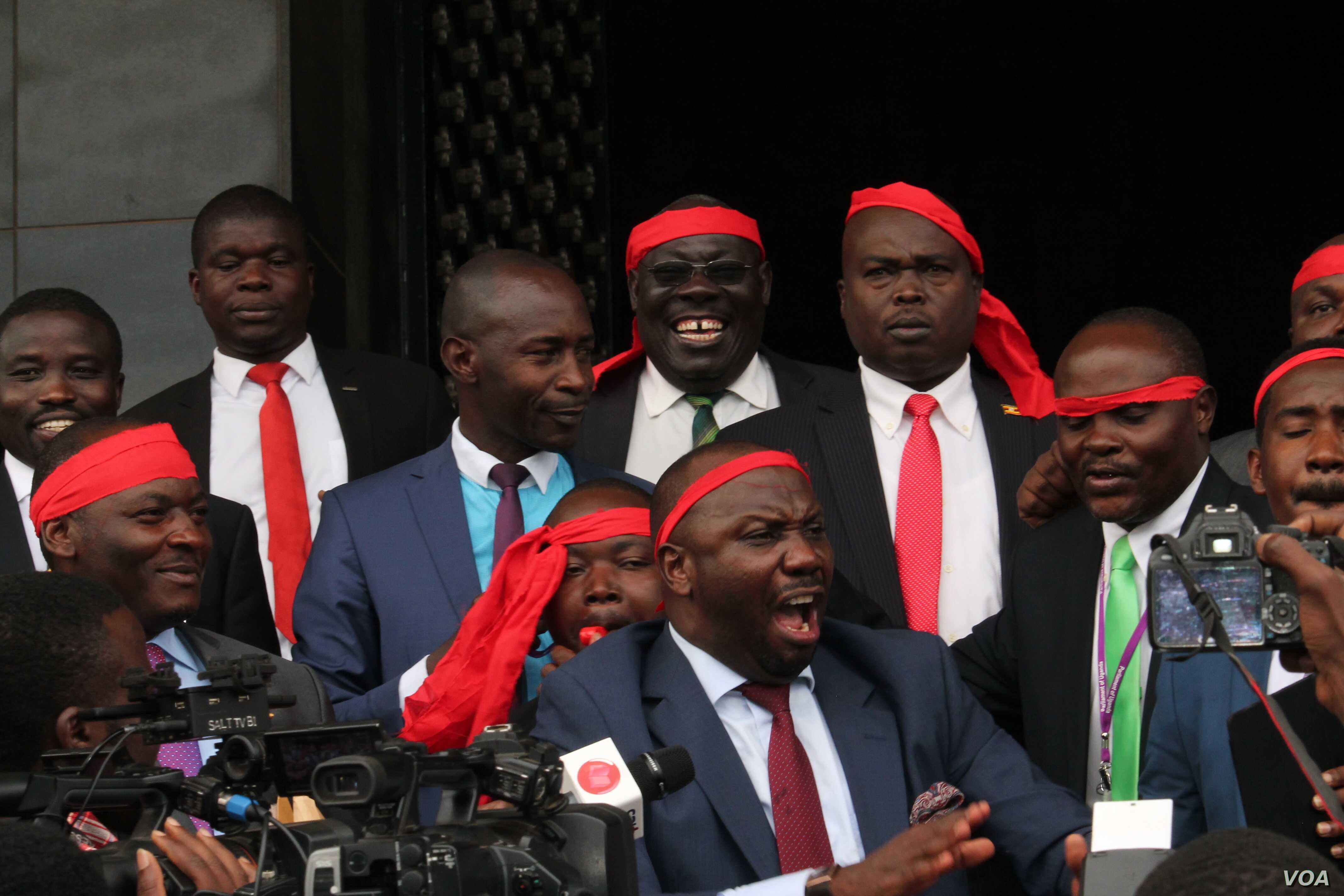 Ugandan opposition legislators sing outside the Parliament building in Kampala, Uganda, Sept. 21, 2017, after a motion to amend the Constitution failed. They left Parliament singing and said every day the Constitution remains untouched is a win.