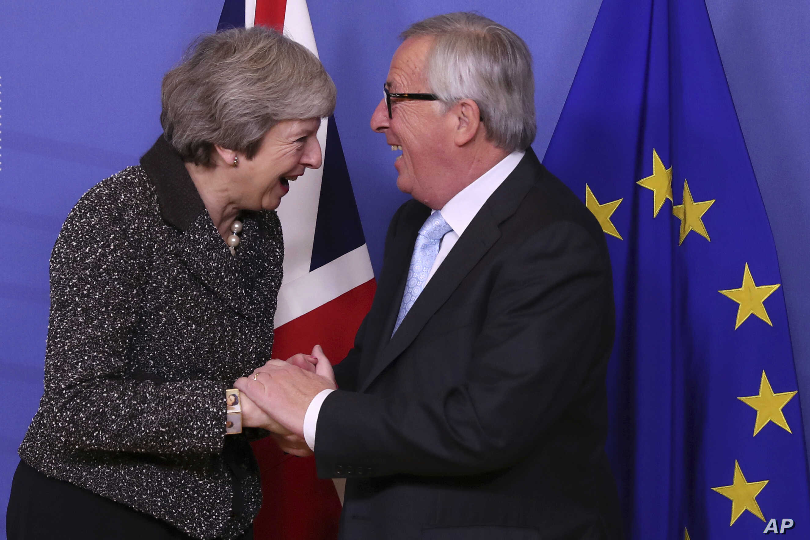 British Prime Minister Theresa May, left, is greeted by European Commission President Jean-Claude Juncker at EU headquarters in Brussels, Dec. 11 2018.