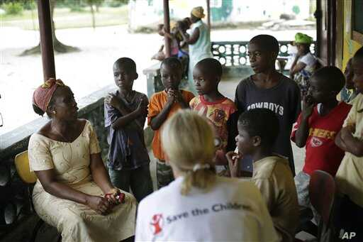 Carolyn Miles, foreground, President & Chief Executive Officer for Save the Children, listens to orphans in Unification Town, Liberia, some 40kms (25 miles) East of the capital Monrovia  Friday Oct. 3,  2014.  The orphanage, run by the Liberian depar...