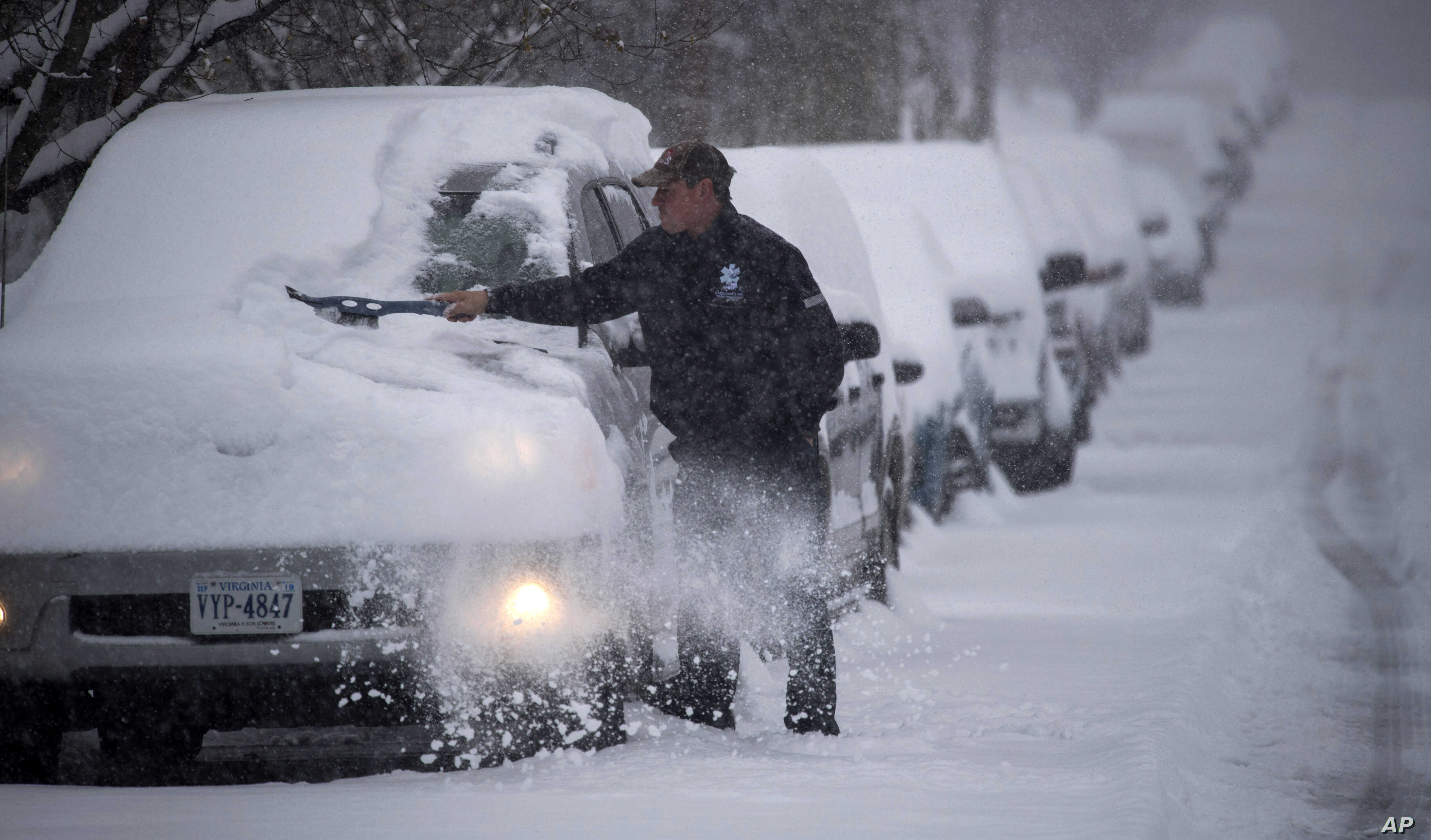 Russ Sprinkel removes snow from his vehicle on Washington Avenue in Roanoke, Va. as snow continues to fall throughout Southwest Virginia, Sunday, Dec. 9, 2018.