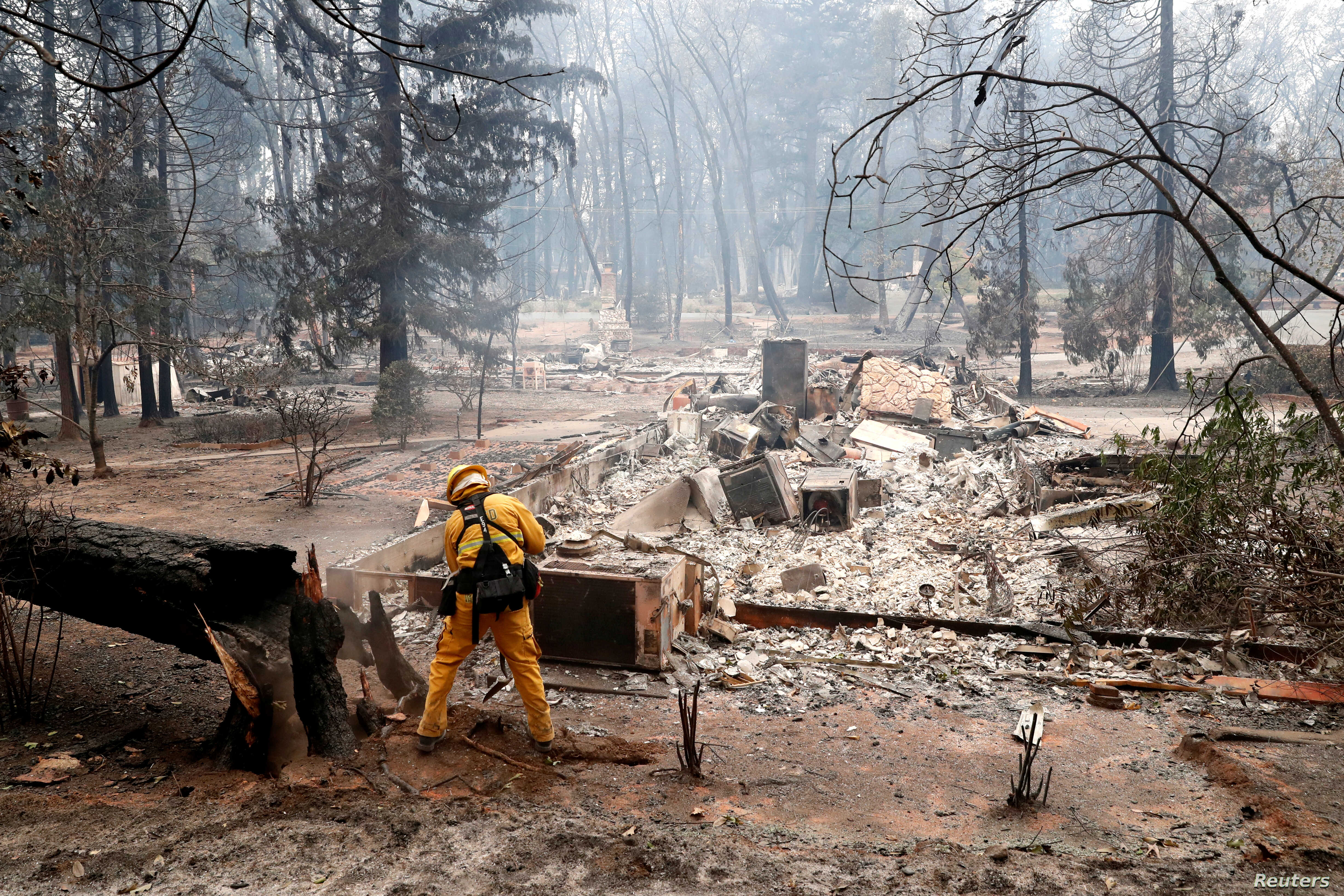 A firefighter extinguishes a hot spot in a neighborhood destroyed by the Camp Fire in Paradise, California, U.S., Nov. 13, 2018.