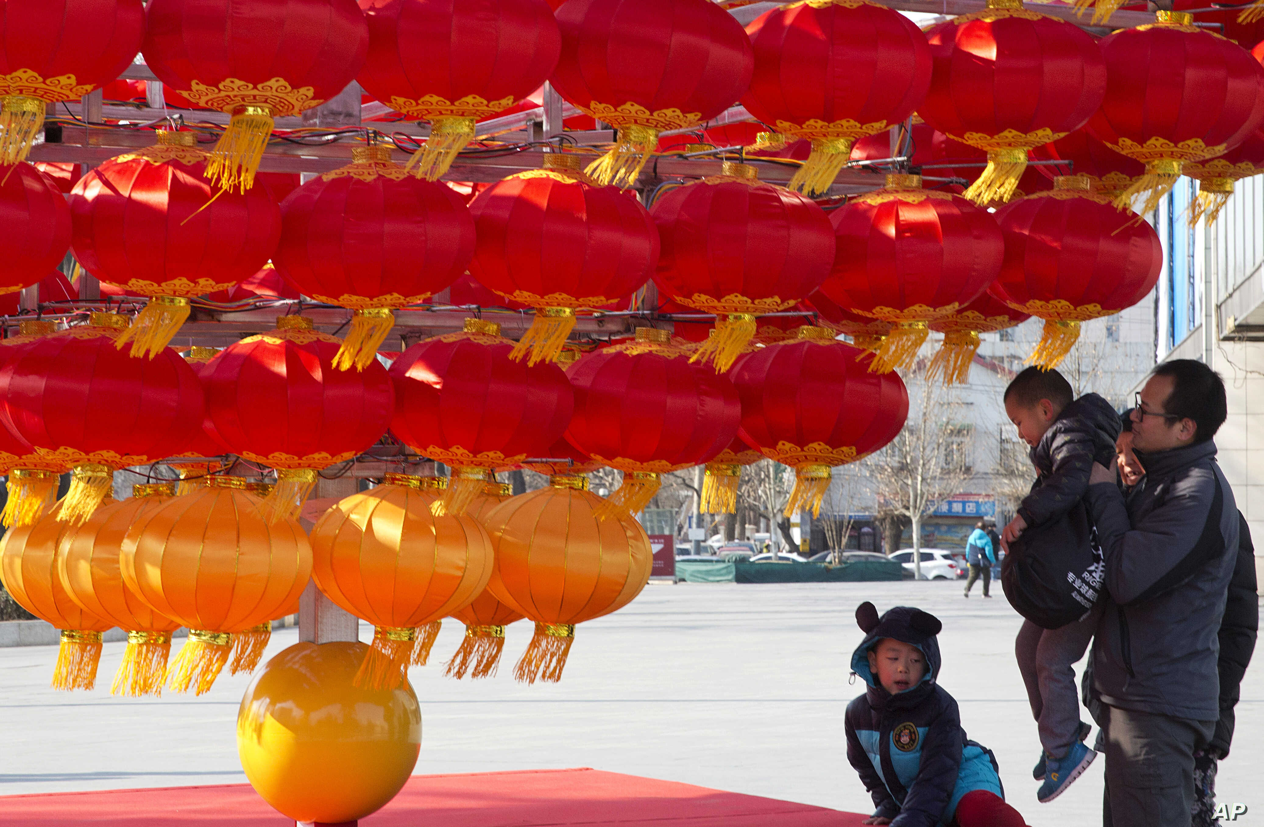 FILE - A man lifts a child up to lantern decorations setup ahead of the Chinese New Year in Beijing, China. China's National Health and Family Planning Commission announced recently that 17.86 million children were born last year, an increase of 1.31...