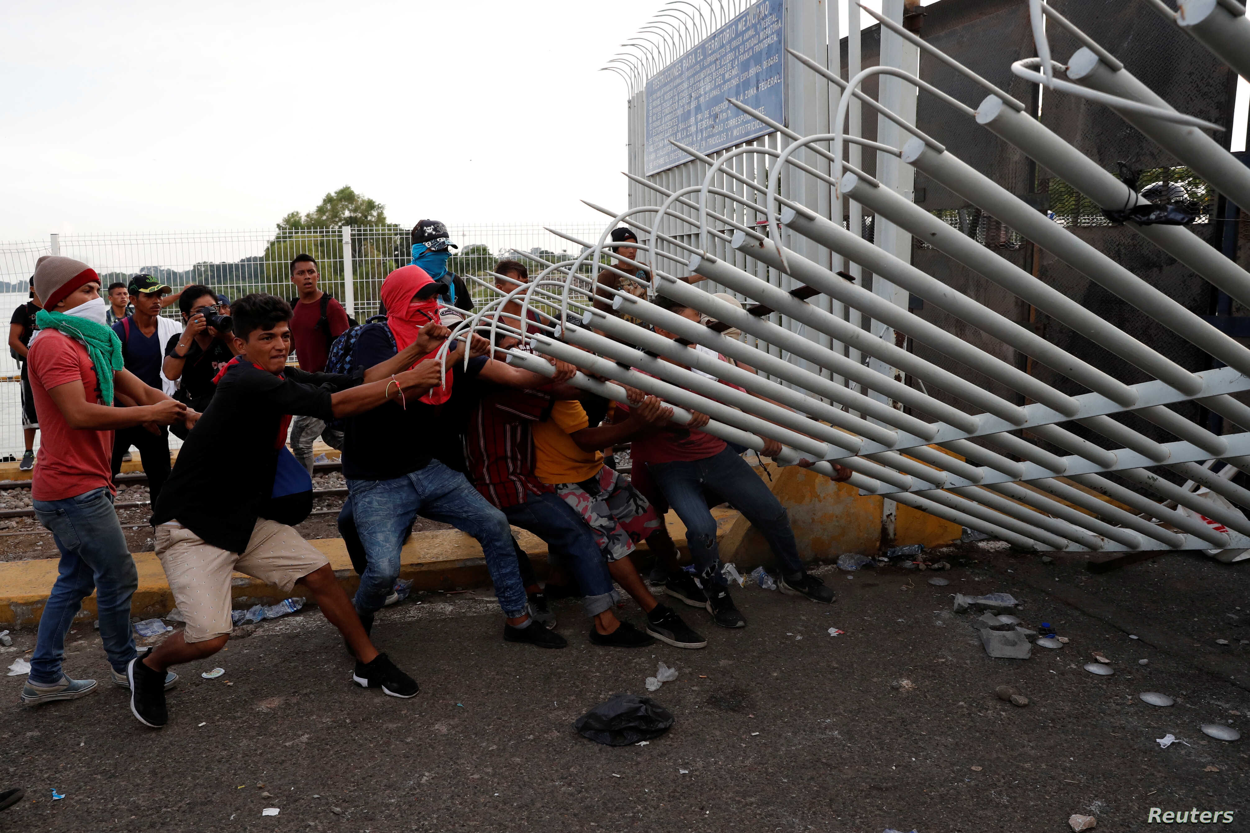 A group of men part of a caravan of thousands of migrants from Central America en route to the U.S, pull down the border gate with the intention to carry on their journey, in Tecun Uman, Guatemala, Oct. 28, 2018.