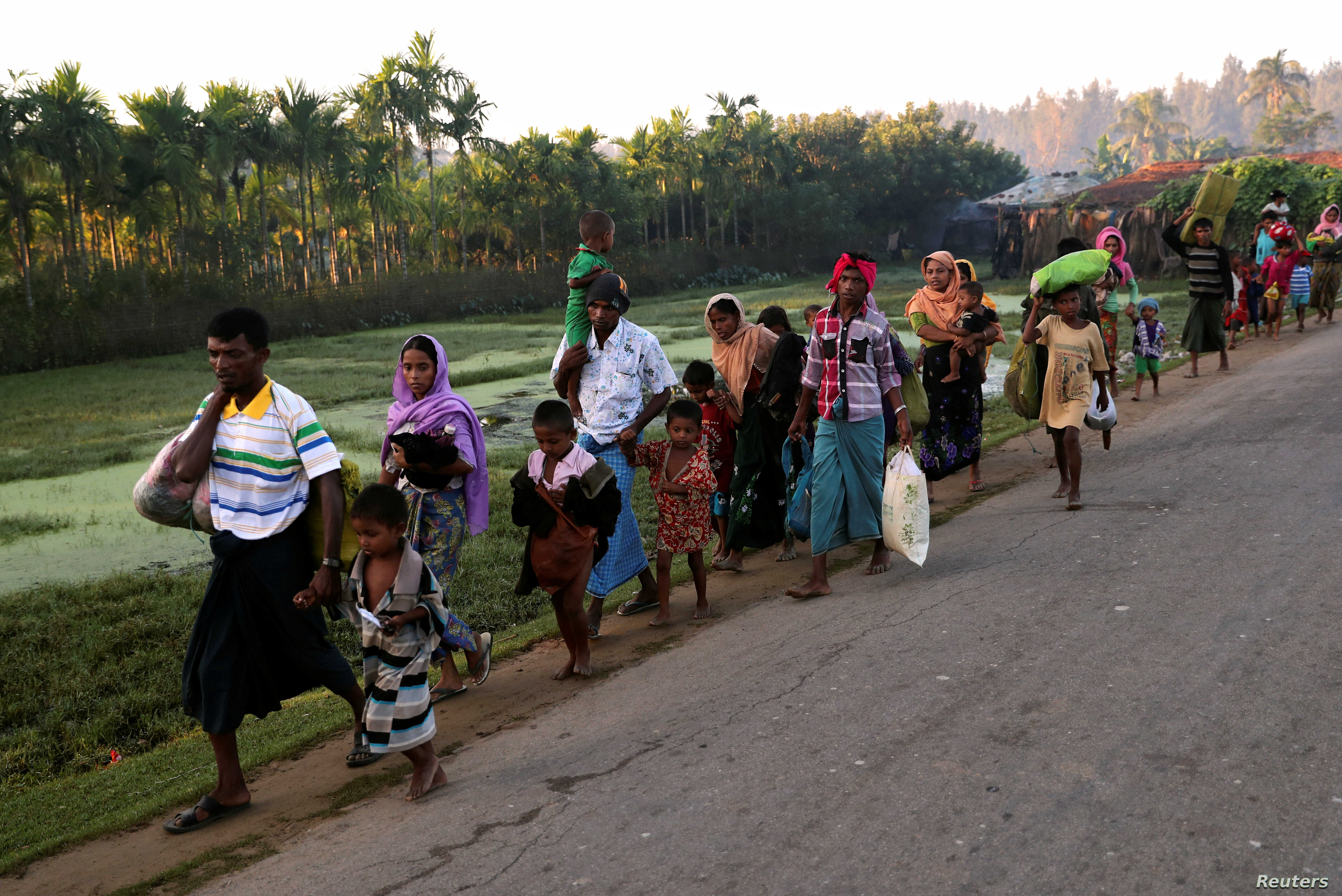 A group of Rohingya refugees, who fled last night from Myanmar by boat, walks toward a makeshift camp in Cox's Bazar, Bangladesh, Nov. 9, 2017.