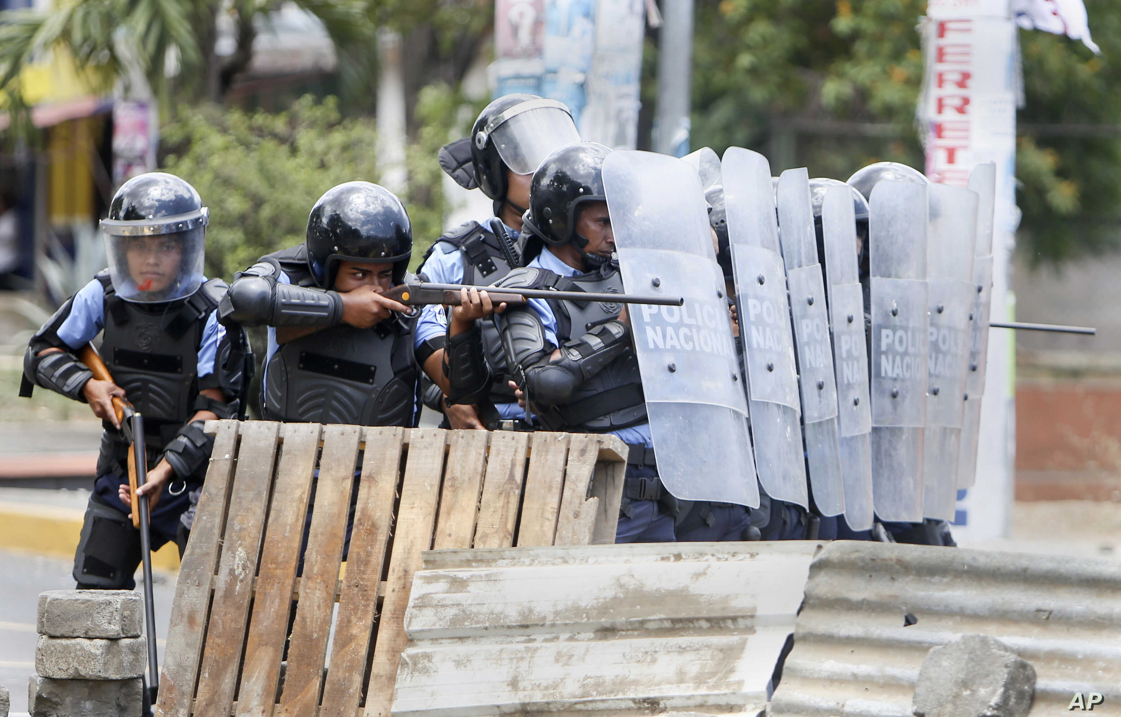 A Nicaraguan police officer aims his weapon at protesting students during a third day of violent clashes in Managua, Nicaragua, April 20, 2018. The Organization of American States have expressed concern over the heavy-handed crackdown, while also cal...