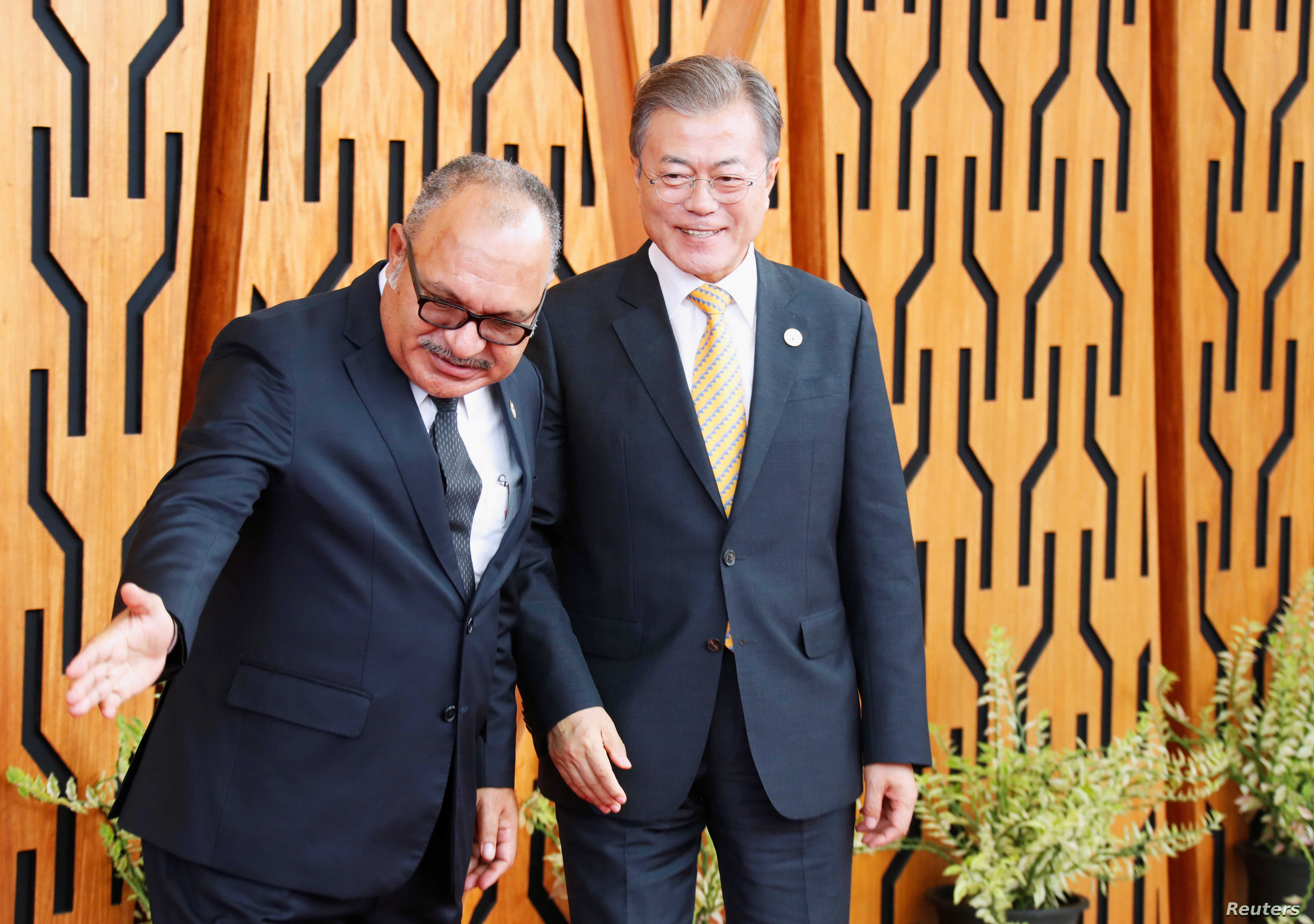 South Korea's President Moon Jae-in is shown the way by Papua New Guinea's Prime Minister Peter O'Neill as he arrives for the APEC Summit, Port Moresby, Papua New Guinea, Nov. 17, 2018. Moon is expected to discuss North Korea sanctions with Chinese P...