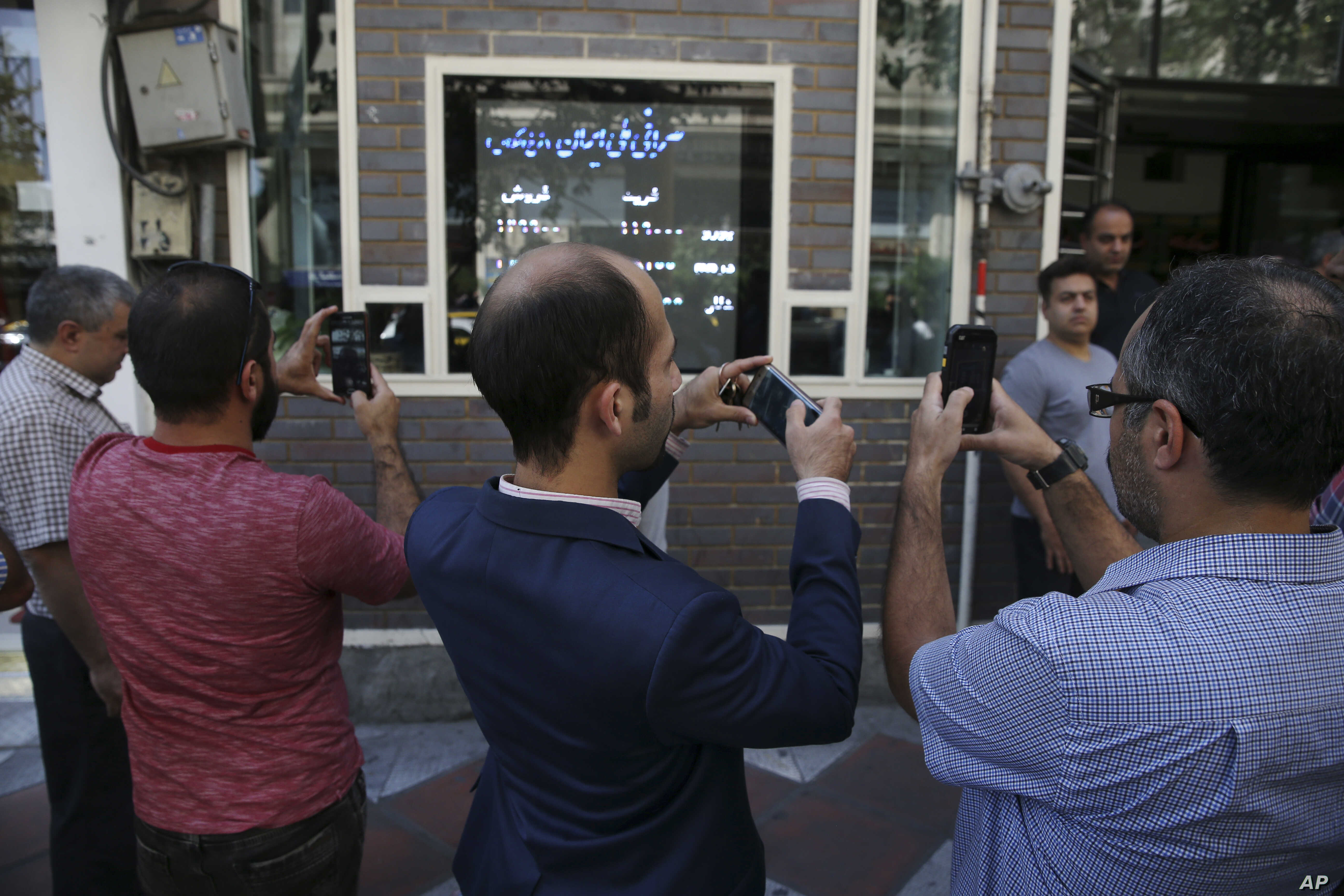 FILE - Iranians take pictures of an exchange shop screen showing various currency rates in downtown Tehran, Oct. 2, 2018. Iran's currency, the rial, had unexpectedly rallied after weeks of depreciation following President Donald Trump's decision to w...