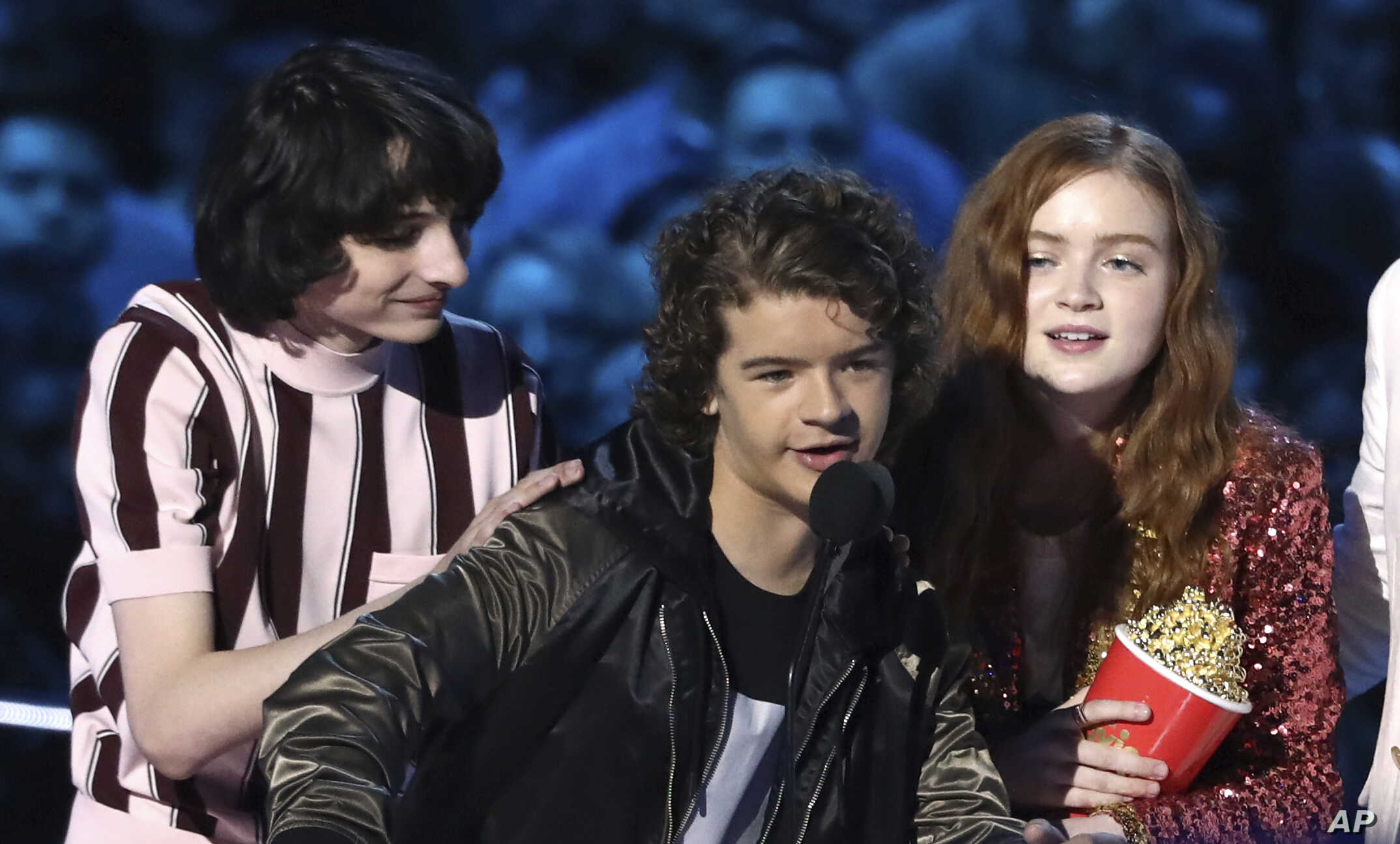 "In this Saturday, June 16, 2018, photo, Finn Wolfhard, from left, Gaten Matarazzo and Sadie Sink accept the award for best show for ""Stranger Things"" at the MTV Movie and TV Awards at the Barker Hangar in Santa Monica, Calif."