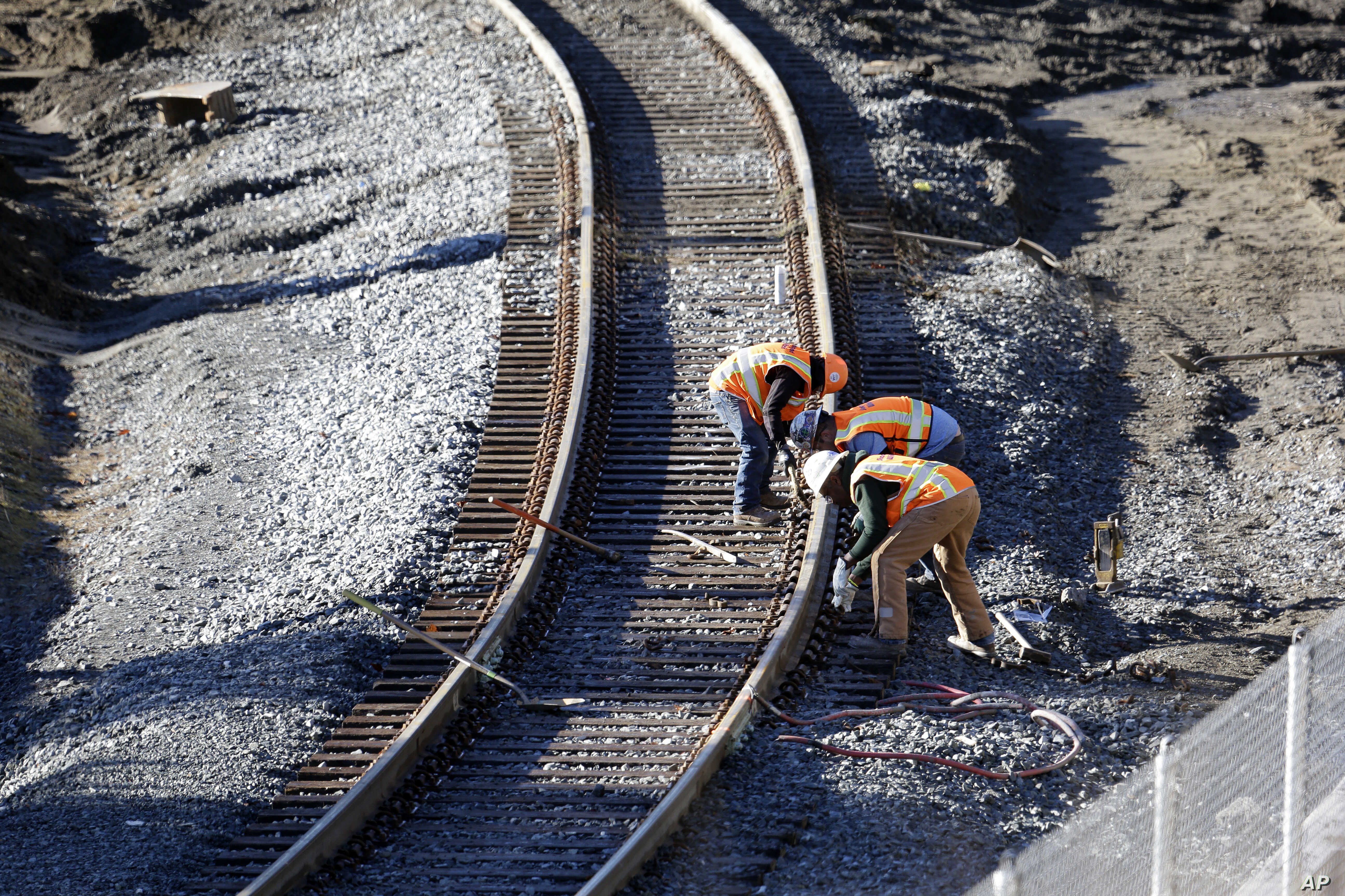 People work at the curve where an Amtrak train derailed onto Interstate 5 two days earlier, Dec. 20, 2017, in DuPont, Wash.