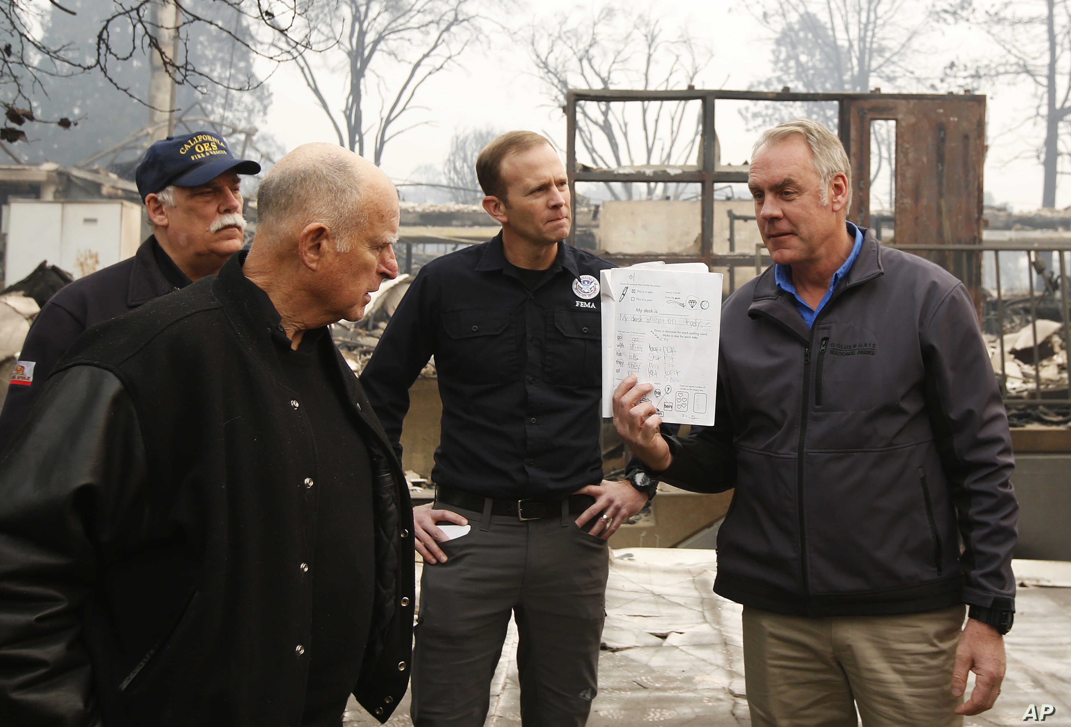 California Gov. Jerry Brown, second from left, looks at a students work book displayed by Interior Secretary Ryan Zinke, that was found during a tour of the fire ravaged Paradise Elementary School, Nov. 14, 2018, in Paradise, Calif. The school is amo...