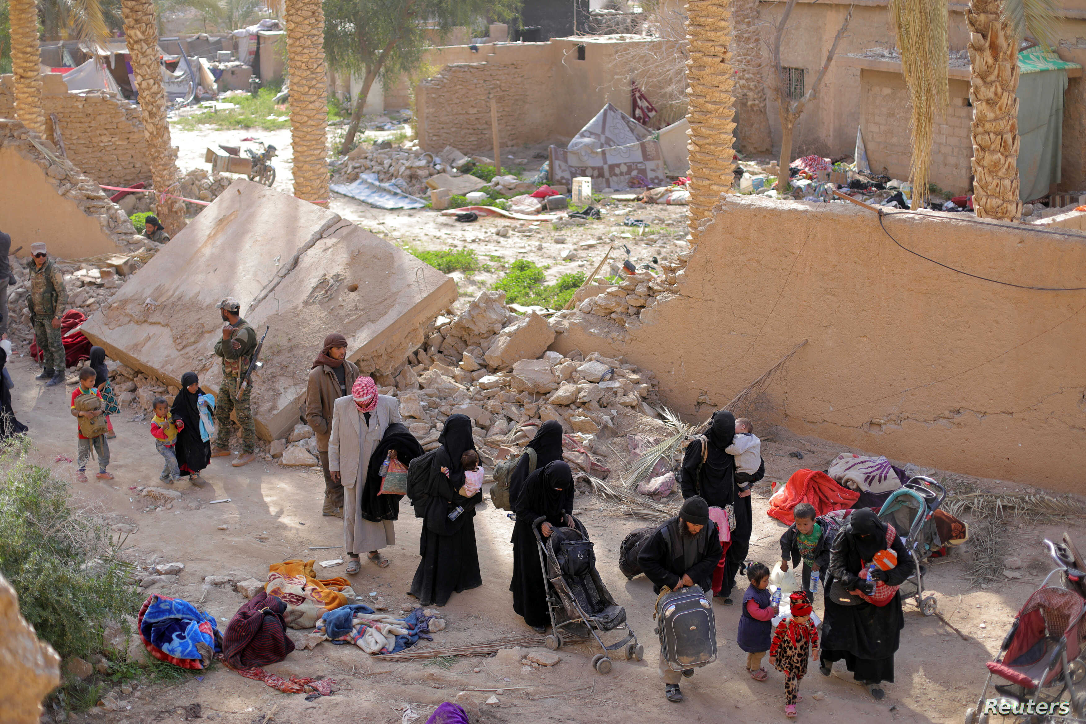 Islamic state fighters and their families walk as they surrendered in the village of Baghuz, Deir Al Zor province, Syria, March 12.
